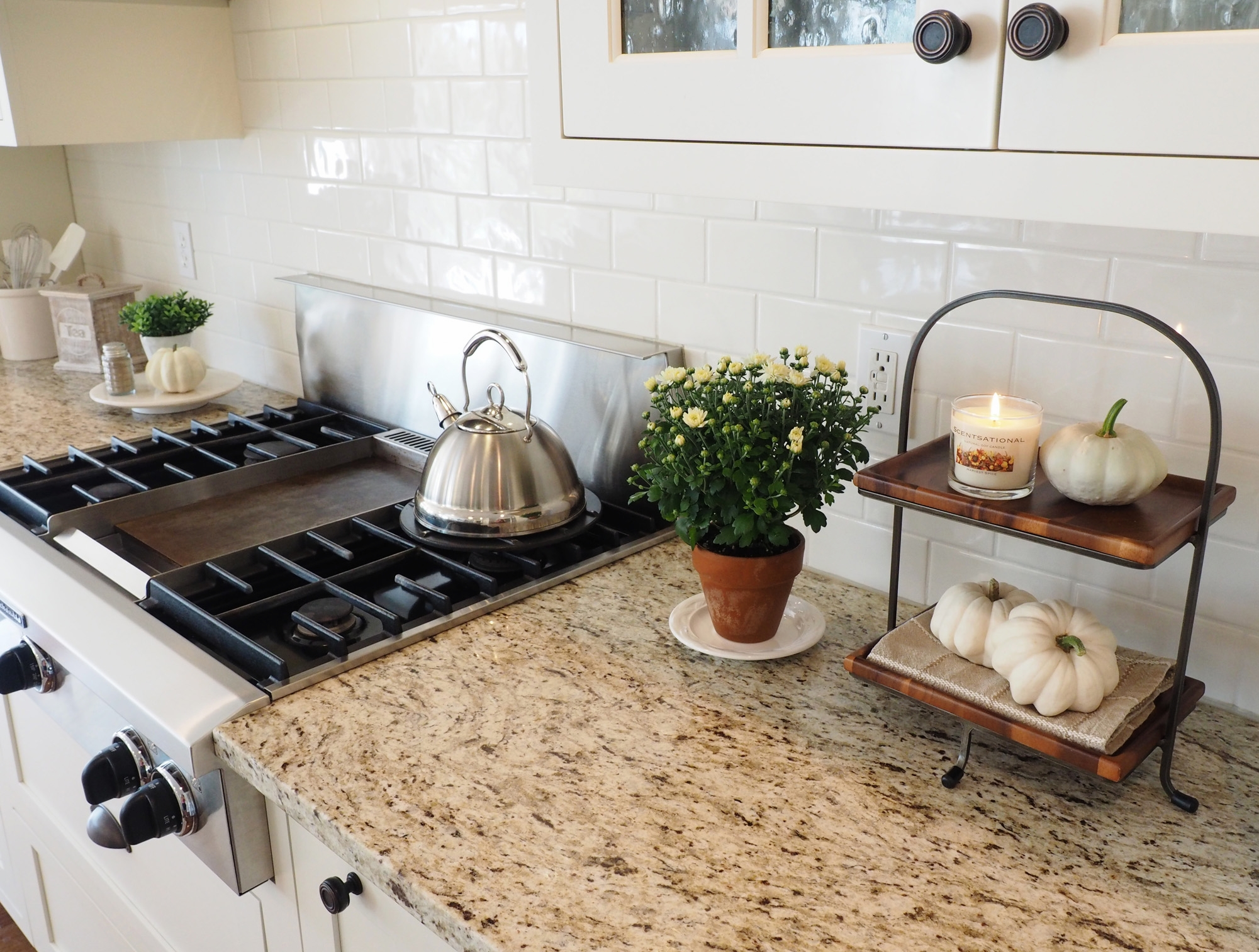 I like to add wood and iron details to my kitchen decor for the fall. It has an earthy feel and goes very well with our granite countertops. The granite is Giallo Ornamental. It's a very neutral granite and looks great with white or off-white cabinetry. It has a creamy background and touches of gray, taupe and dark brown. It truly is one of my favorite granite choices and I believe readily available and within an affordable price range. Our gas cooktop is made by Kitchen-Aid featuring the center griddle. I have fried hamburgers, made pancakes and grilled cheese sandwiches on our griddle with ease however,since our children are gown now,my use for it has declined. Today I would opt for the 6 burners. But hey, you never know what life will bring your way when making these choices.