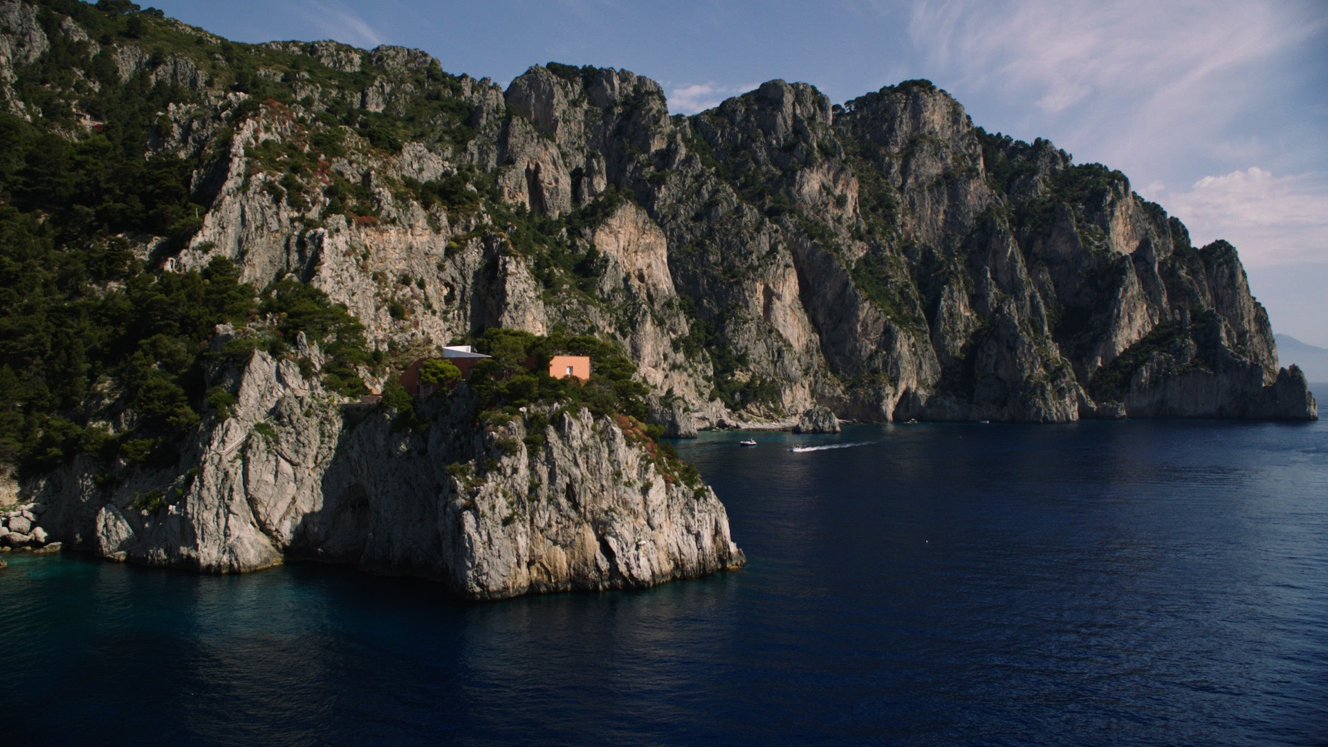Built on the edge of the cliff, it is a brick box built to withstand stormy winters as the waves often reach the crest of the rock and slam the front of the house. The house is often used for serious study and writing and is still owned by Malaparte's family.