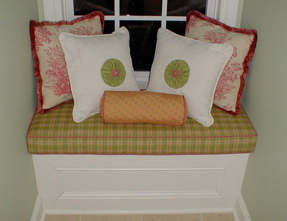Rosettes on white pillows, roll pillow and box cushion fabricated by Complimentary Designs.