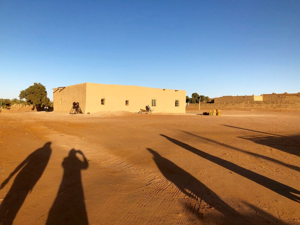 Muhammed's home. And our long shadows - that's me, second from left.