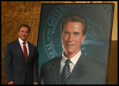 Former California Gov. Arnold Schwarzenegger poses next to his portrait. (Photo by Justin Sullivan/Getty Images)
