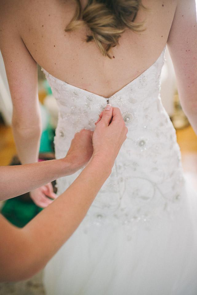NH Wedding Photographer: bride putting on dress