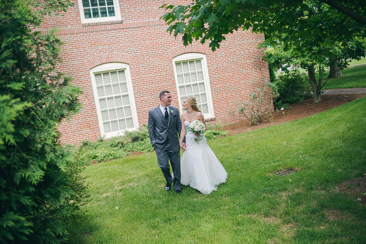 NH Wedding Photographer: bride and groom walking at Saint Anselm