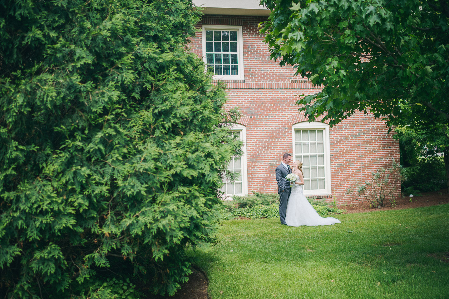 NH Wedding Photographer: couple in garden against old brick