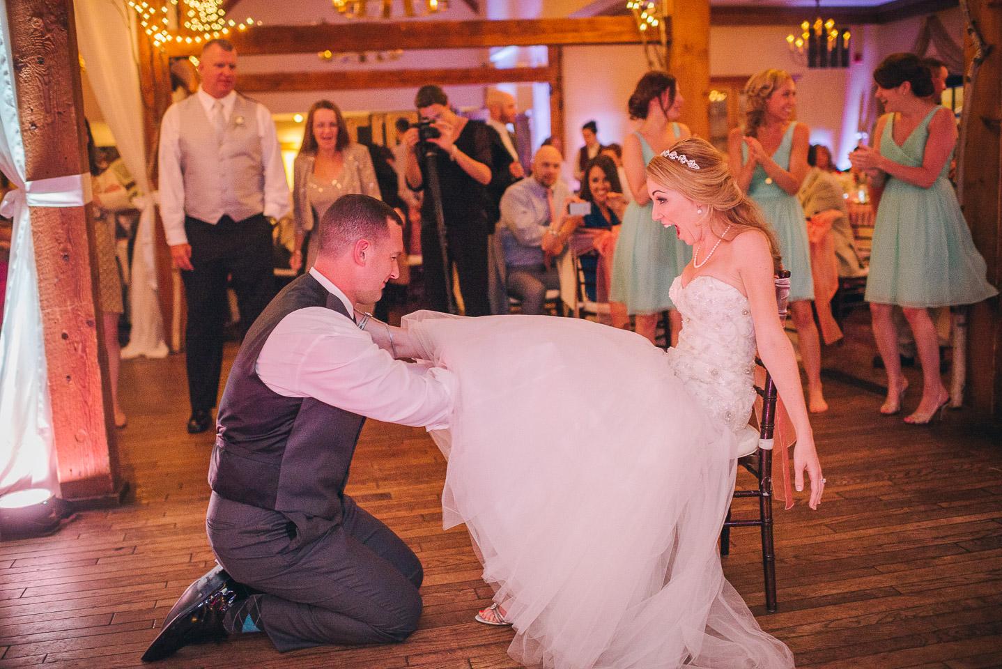 NH Wedding Photographer: groom takes garter
