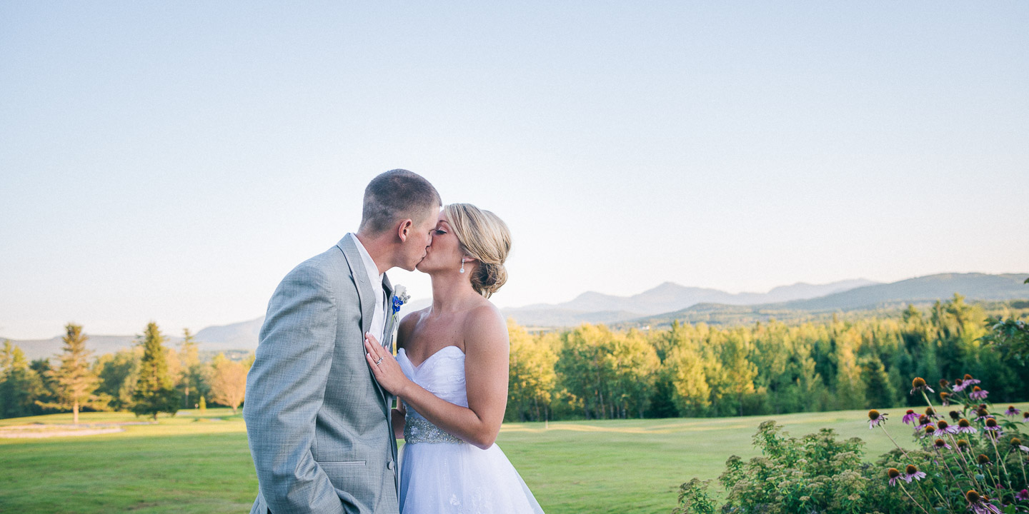 NH Wedding Photographer: groom kissing bride in the mountains