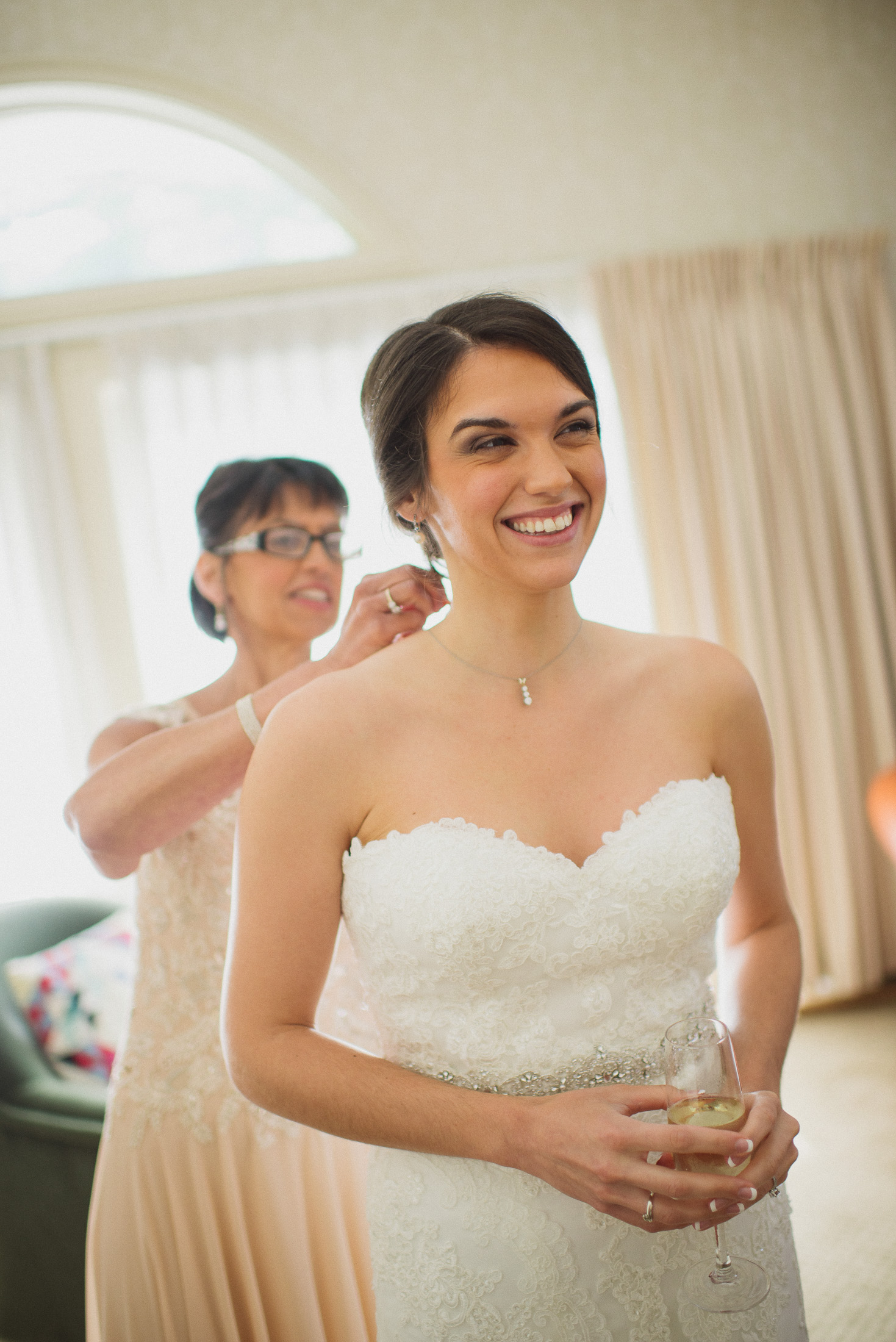 NH Wedding Photographer: mother putting on bride's necklace