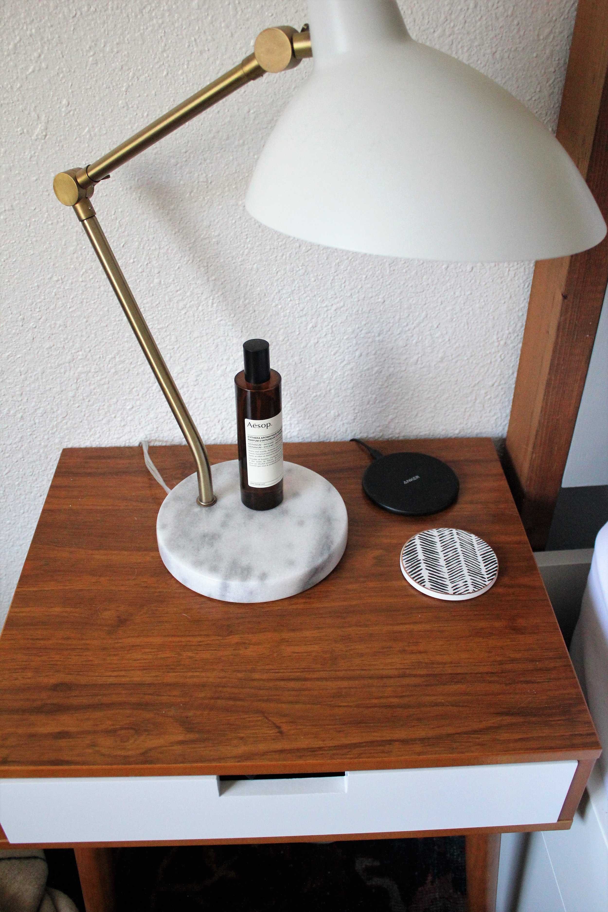 Bedside must haves - a Marble and Brass lamp, Aesop room spray, and a wireless charger