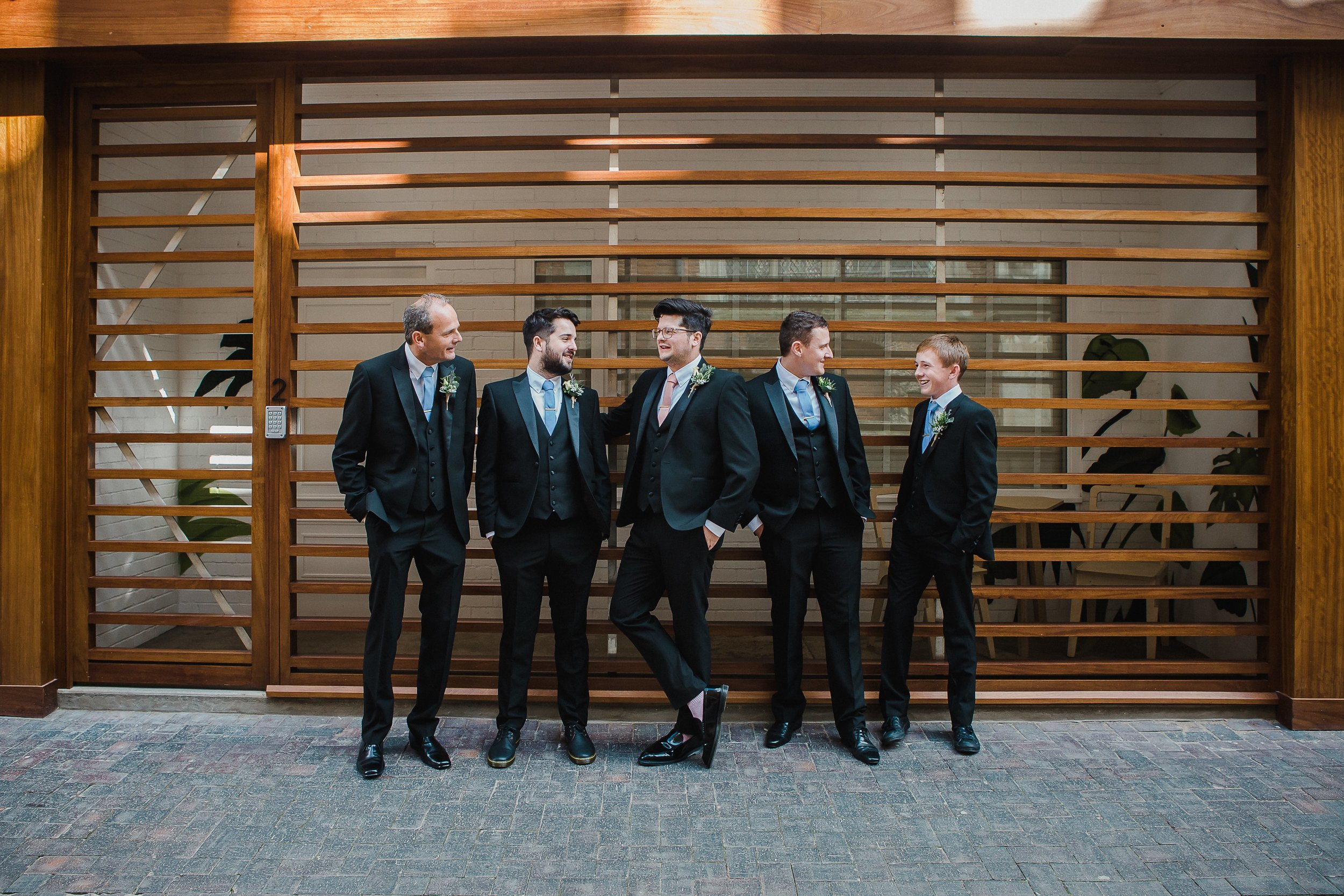 Featured: Hideout Groom, Nick (middle) & groomsmen outside Hideout Hotel