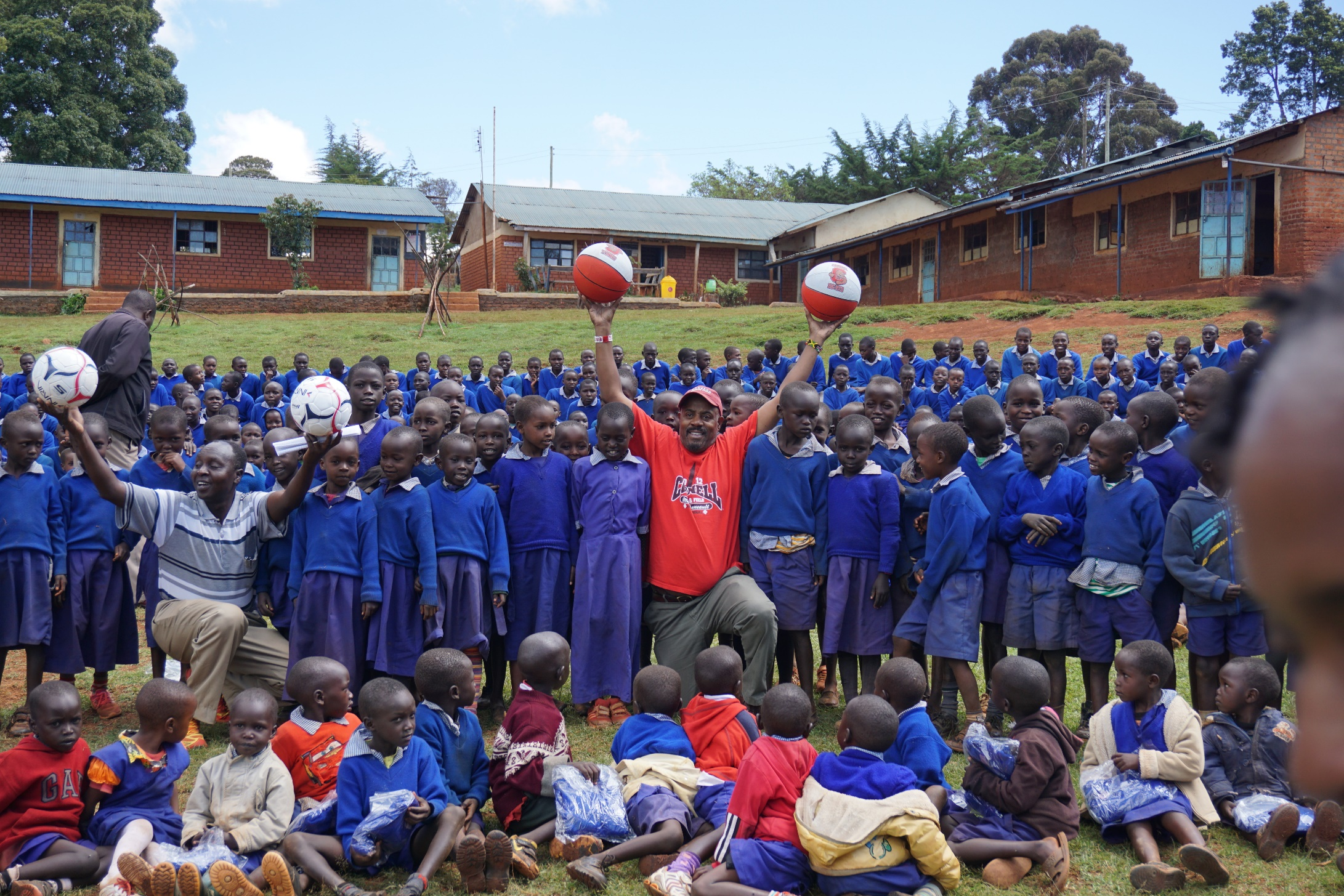 CWA director Kevin Thompson distributing soccer and basketball's with Kamariny School Principal Robert Kiptoo