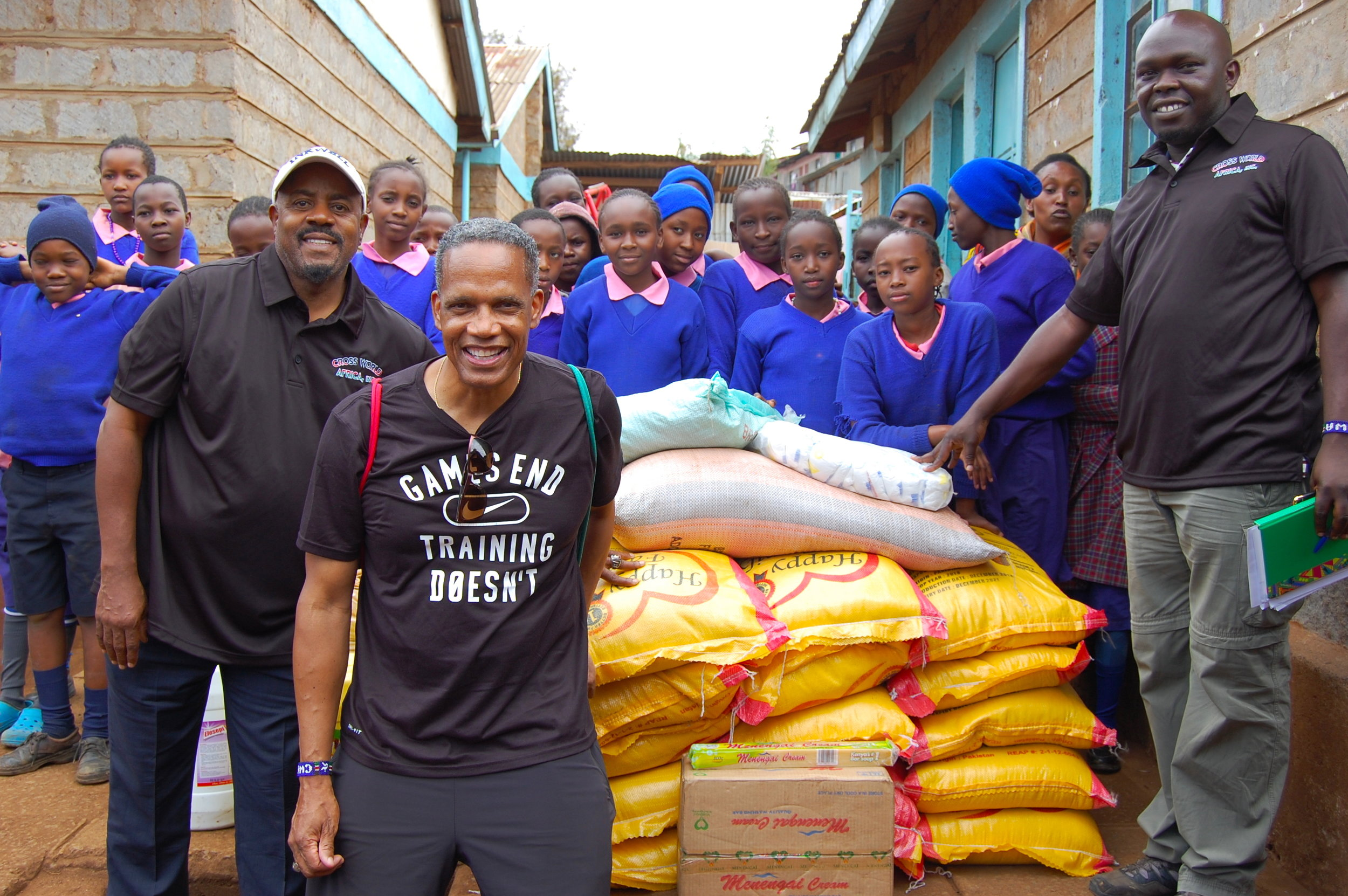 From left to right: founder Kevin Thompson, President Eric Garvin, and Project Leader Kenneth Owade with Cross World Africa's food donation of maize, beans, and rice-staples of the Kenyan diet.
