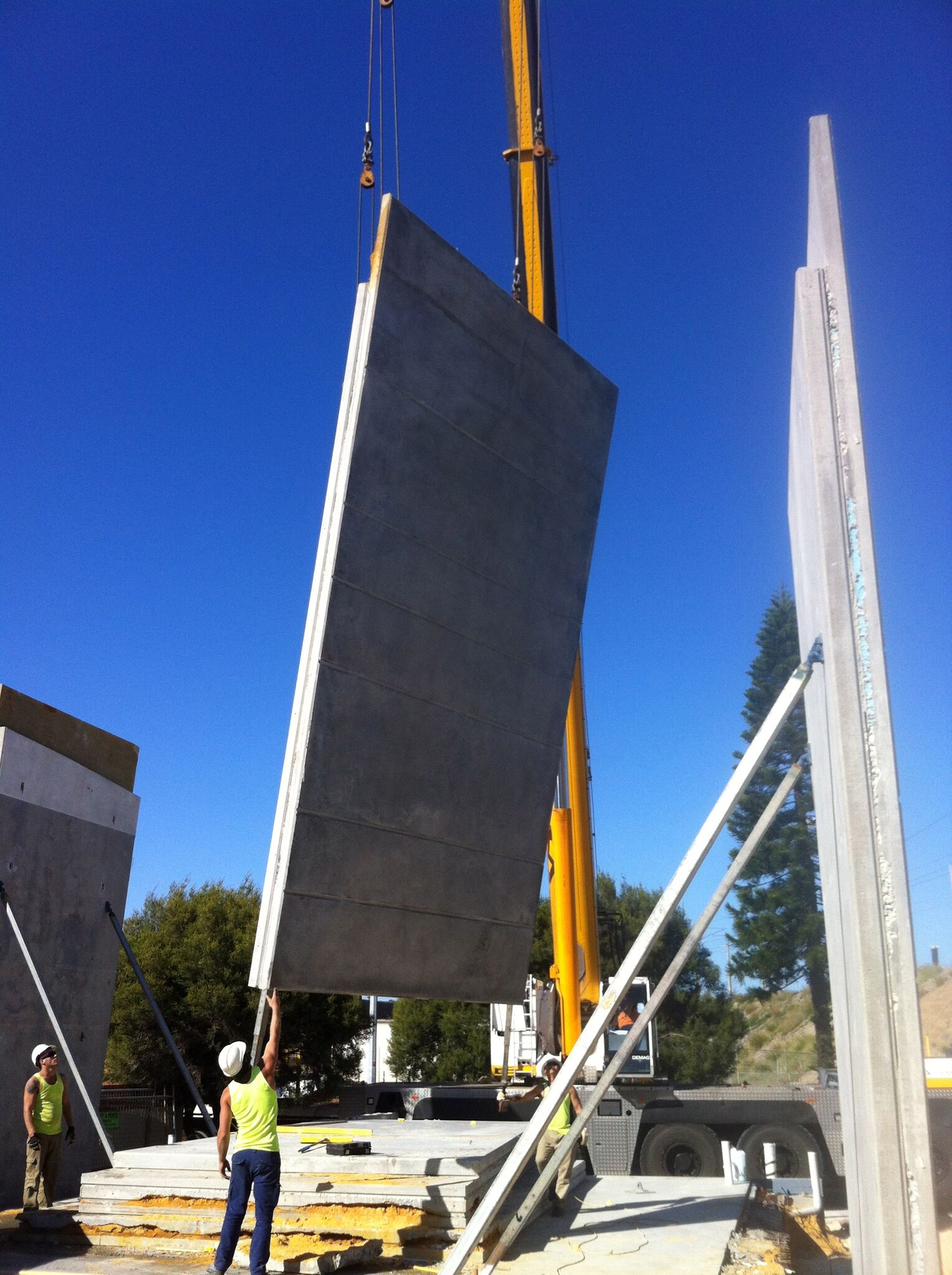 Concrete panels are lowered into place during construction.