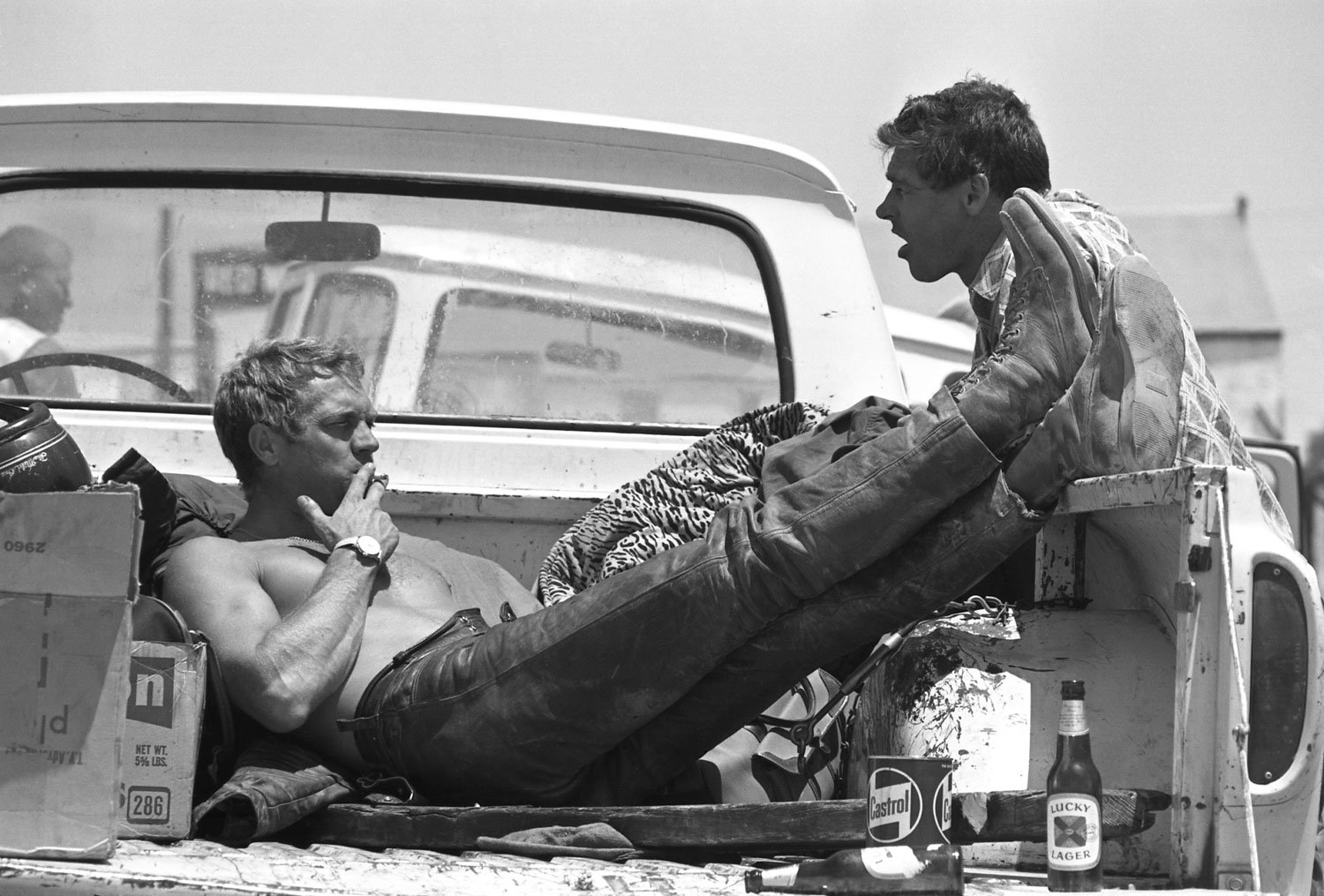 Steve McQueen relaxing in a pickup truck with a few Lucky Lagers