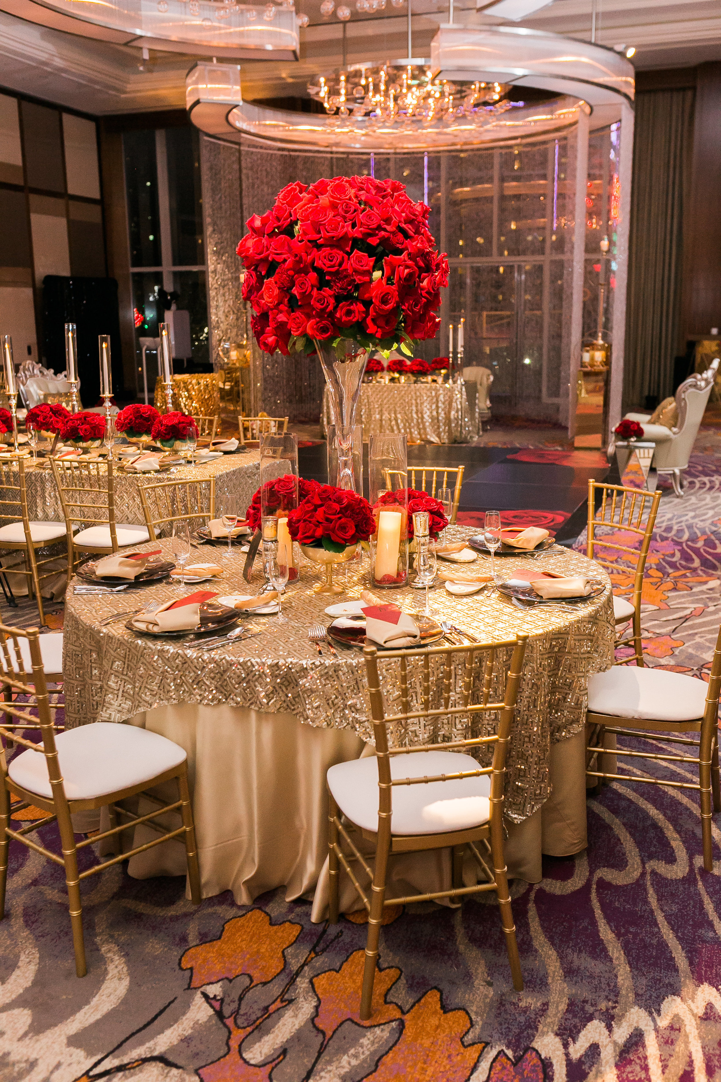 Gold tables topped with tall red rose centerpieces.  Las Vegas Wedding Planner Andrea Eppolito.  www.andreaeppolitoevents.com  Photo by J.Anne Photography.  www.j-annephotography.com  As seen on The  Wedding Editorialist  Wedding Blog.