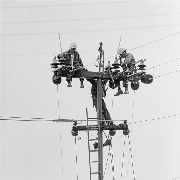 Workers at high tension tower