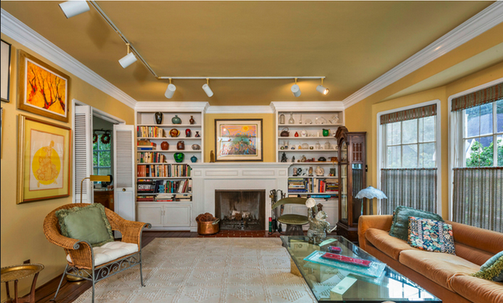 The fireplace and built in shelving make this den one trip to the bookstore short of a study. Also breached through a double collapsing door, the transitions through the rooms are dramatic. The crown molding is the design highlight of the den, remade and repainted over the years.