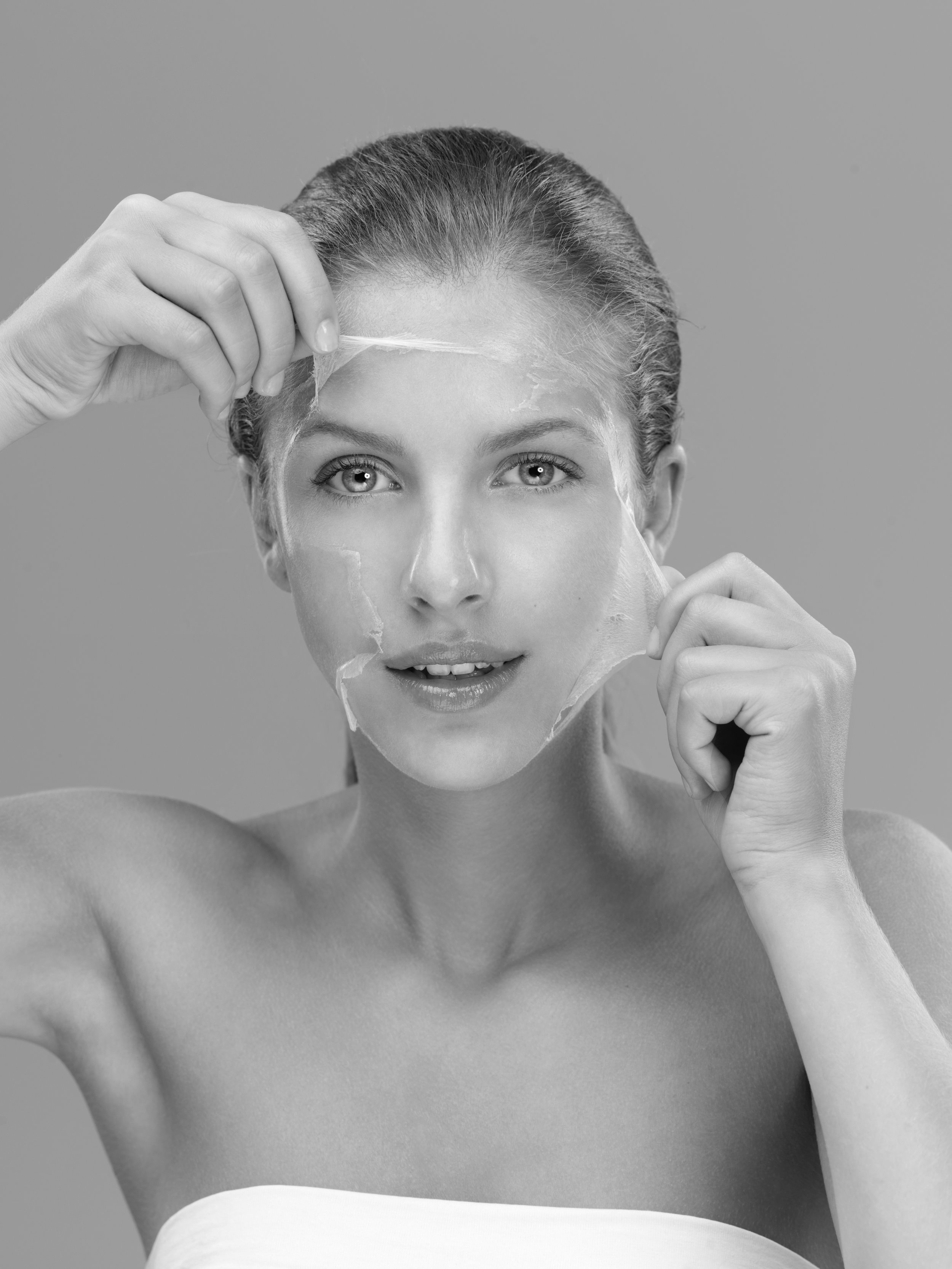 young-woman-taking-off-peeling-mask-P9ZSJBW.jpg