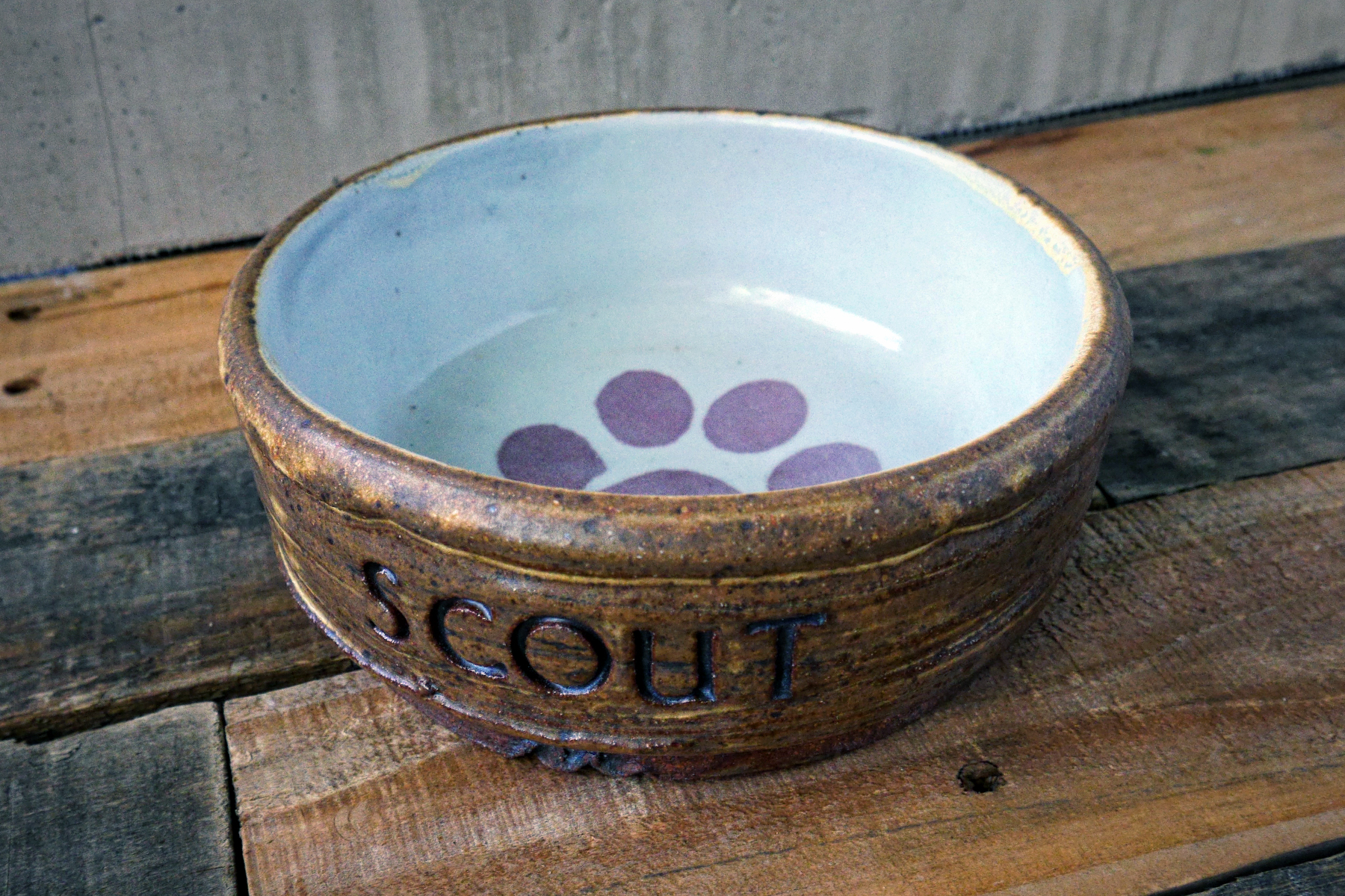 Medium pet dish in yellow salt with with custom text andred paw print on white.