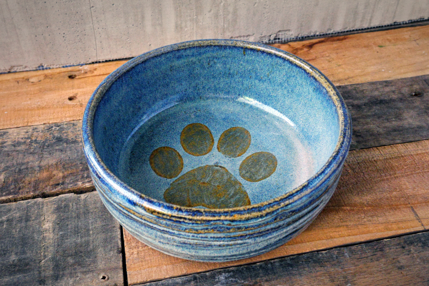Large pet dish in rusted blue with iron paw print on rusted blue.
