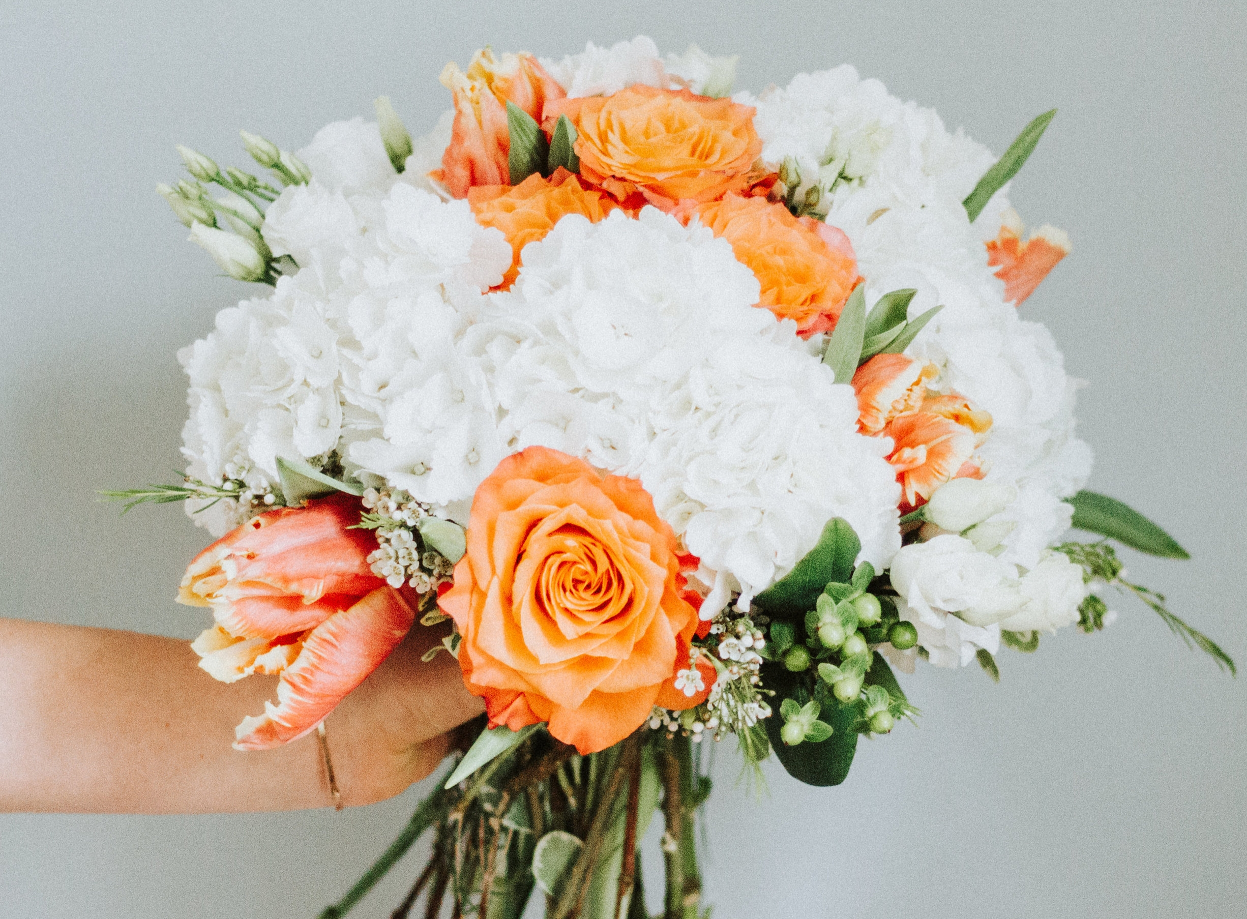 Love & Luster Floral Design White Hydrangea Bouquet with orange roses, tulips and berries