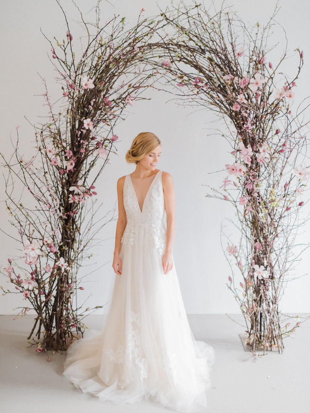 Bride with magnolia wedding arch Luster Floral Design at Sinclair and Moore Workshop, photo by Kristen Honeycutt Photo Co.jpg