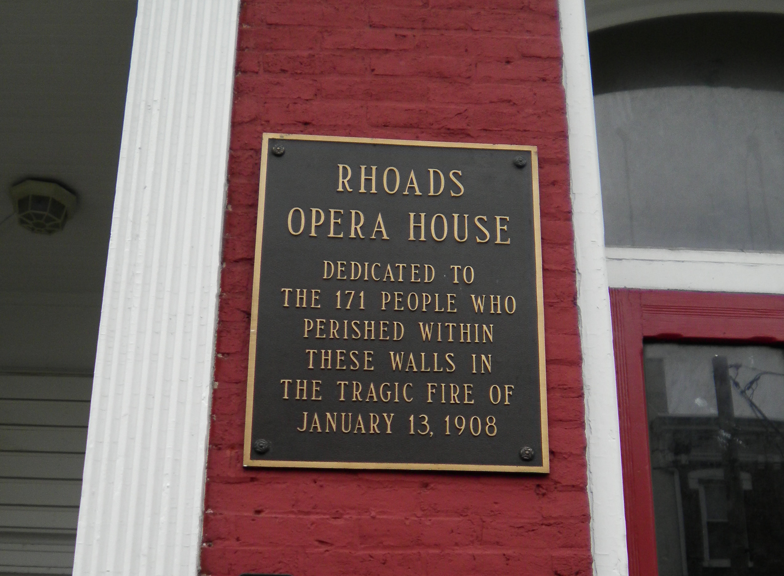 """The plaque on the former site of the Rhoads Opera House - """"Dedicated to the 171 people who perished within these walls in the tragic fire of January 13, 1908""""."""