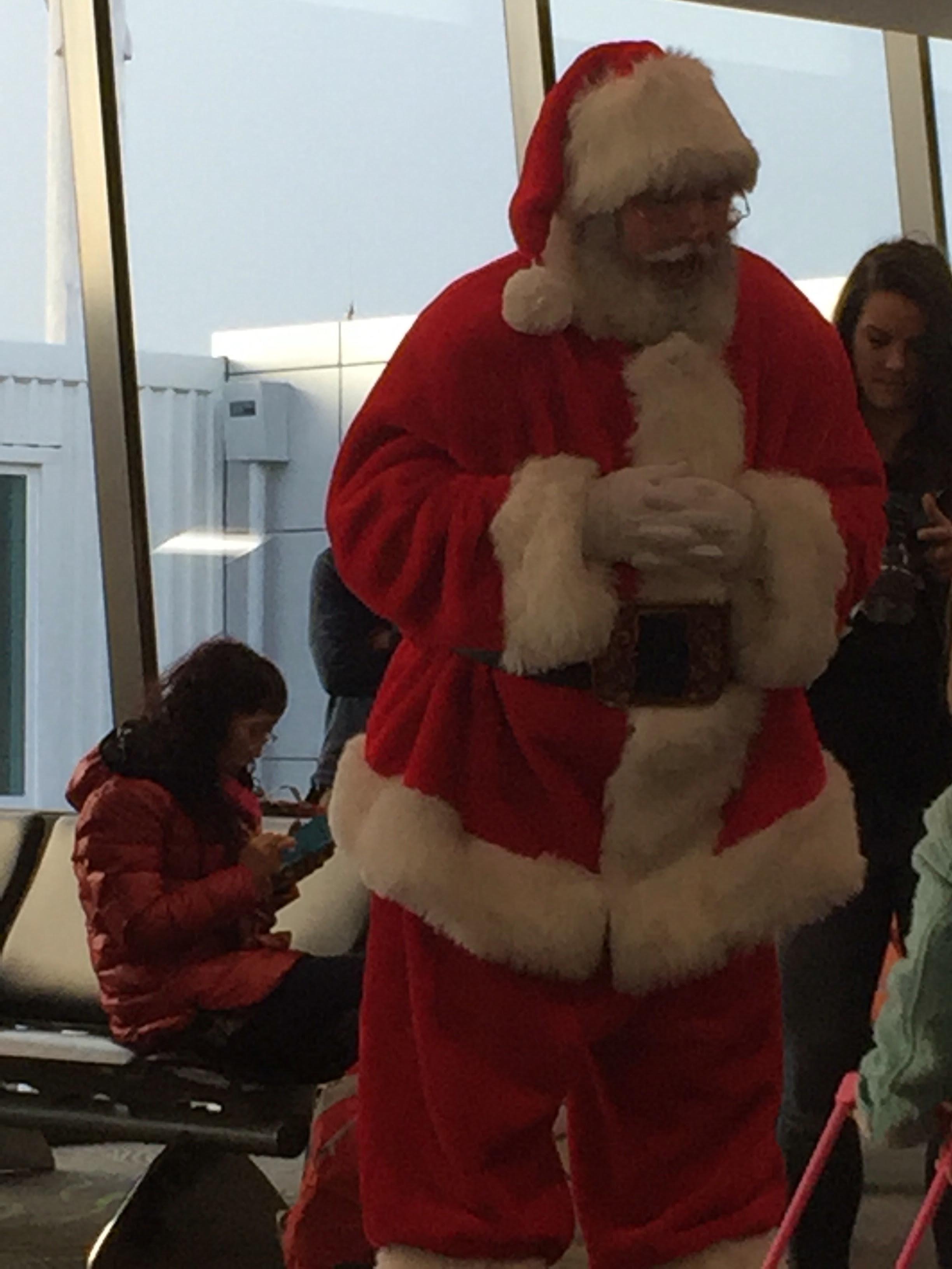 SANTA CONVERSING WITH KIDS AT THE AIRPORT