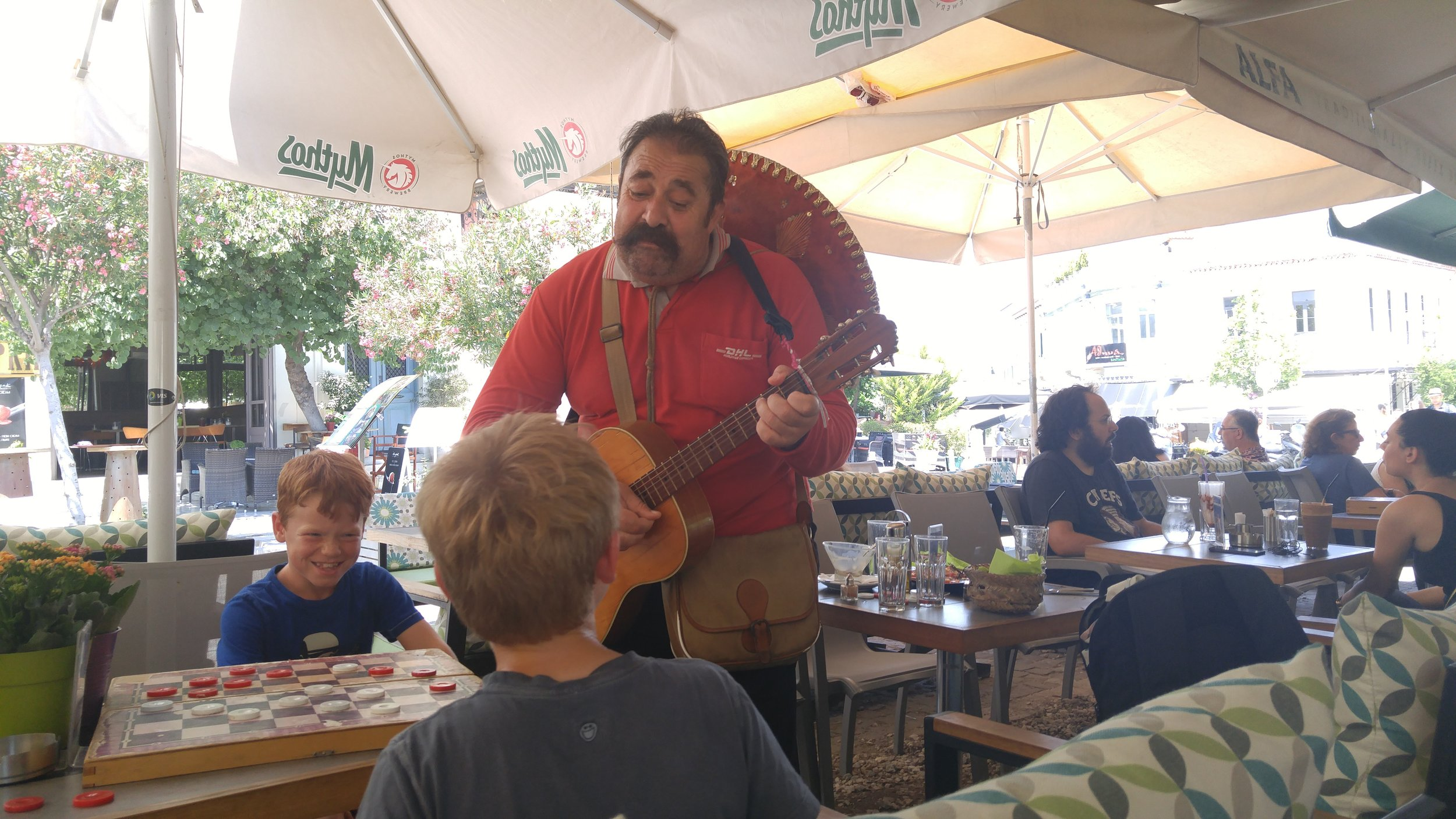 My nephews are serenaded by a street performer while playing checkers at a cafe in Thiseio.