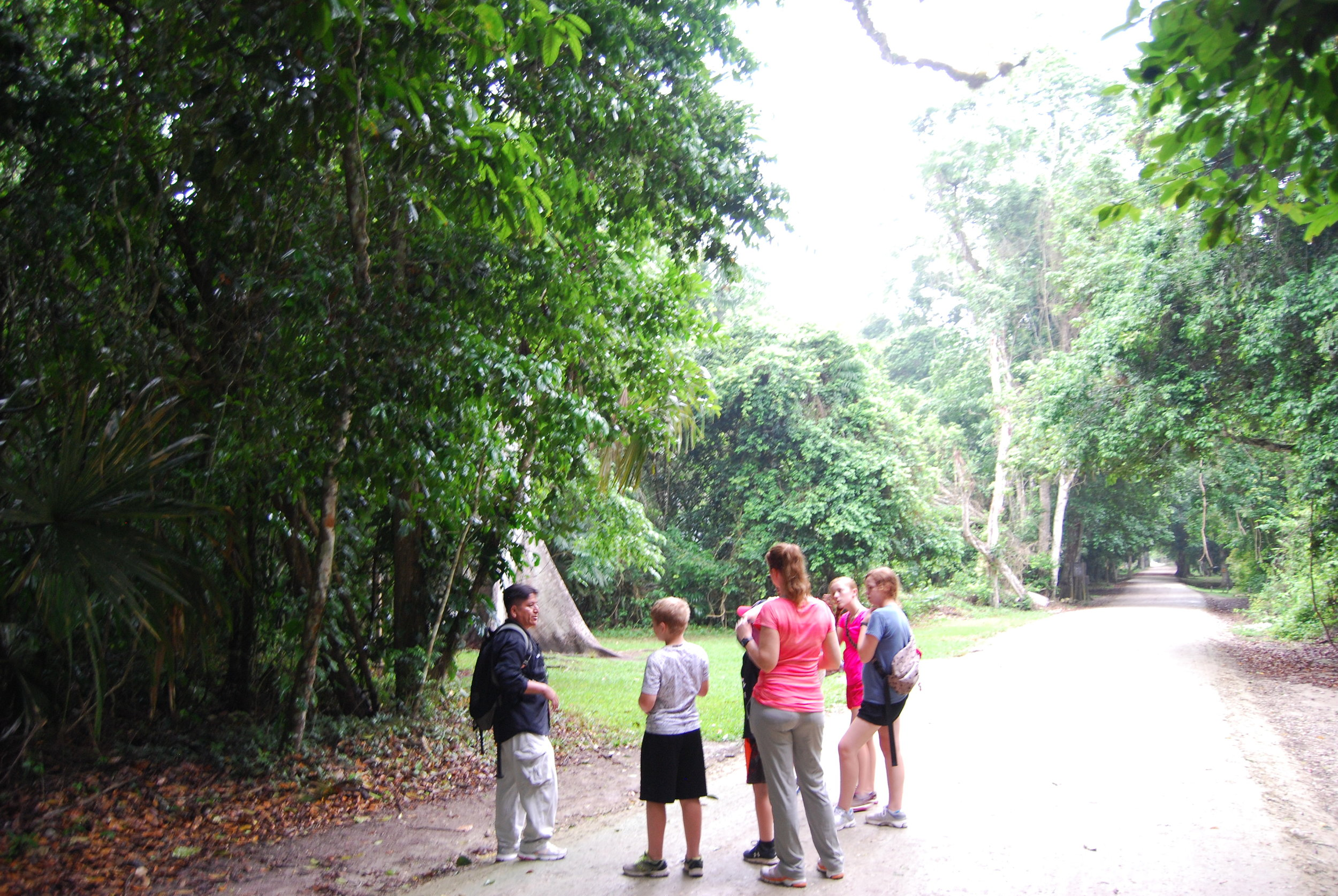 The family listing intently to our guide explaining the importance of the ceiba tree to the Mayans.