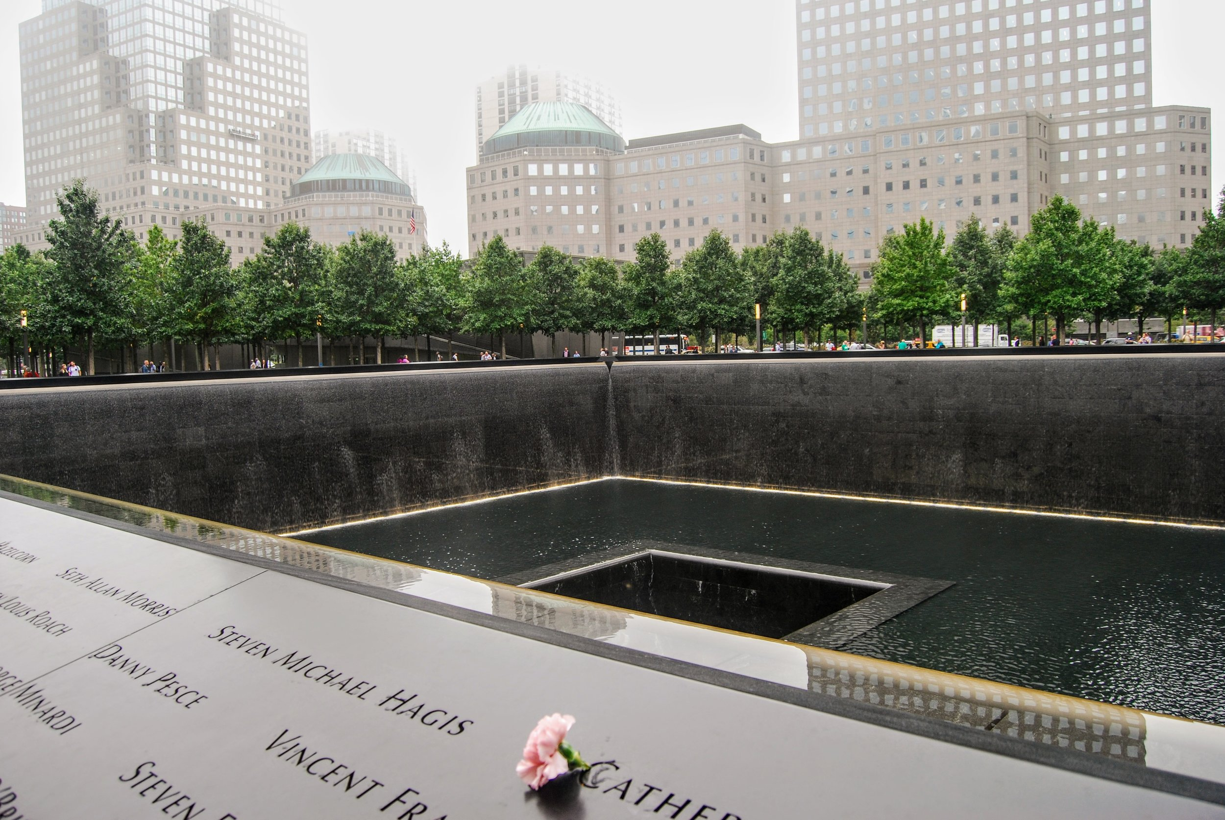 The 9/11 Memorial next to the Museum. The two waterfalls encapsulate the original footprints of the Twin Towers and each victim's name is inscribed on the surrounding walls.