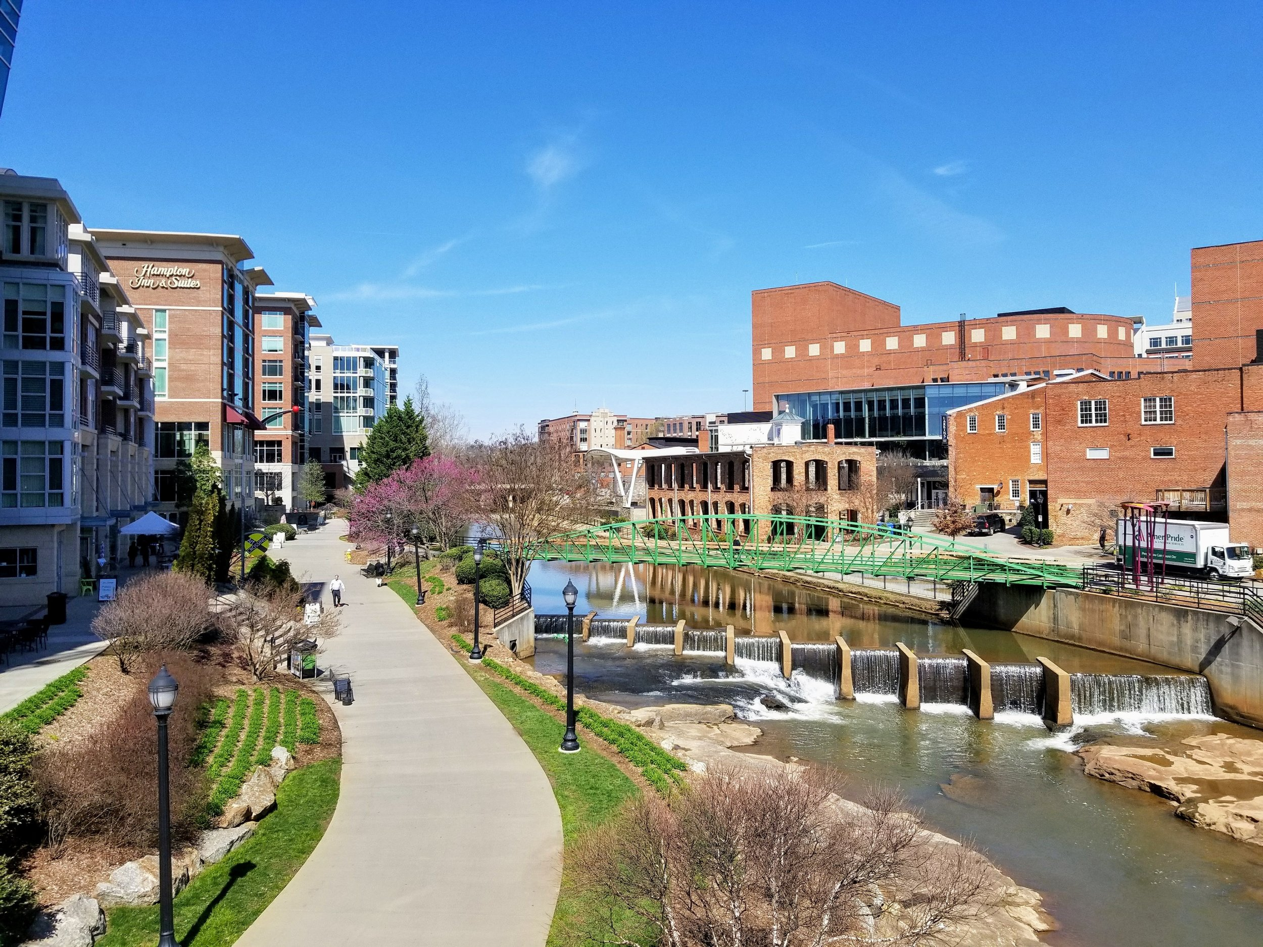 Downtown Greenville with Hampton Inn and Suites seen on the left and the awesome Swamp Rabbit Trail as it follows along the Reedy River.