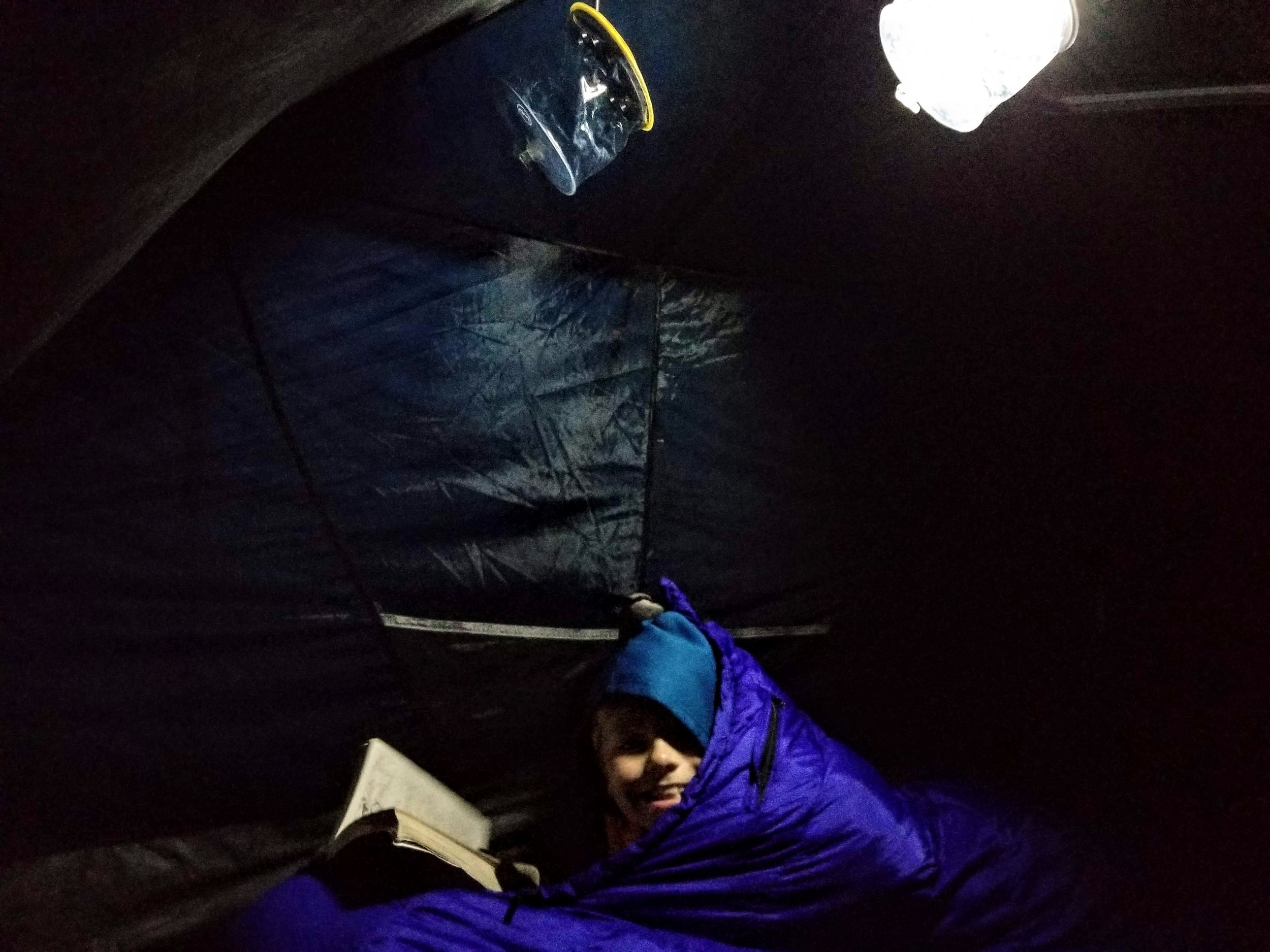 Reading by the light of a Luci light in the tent.