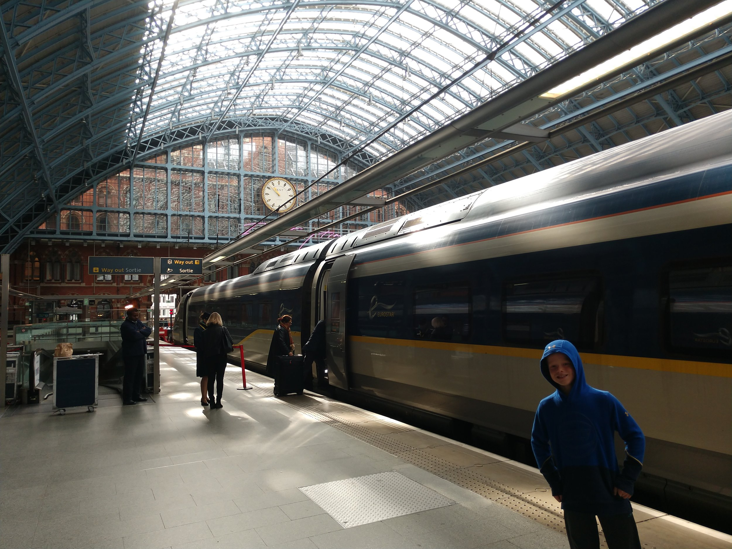 Outside the Eurostar in St. Pancras station. There is a mad rush to board but then the platform kinda clears out. The escalators up from the waiting room are on the left, behind the attendant.