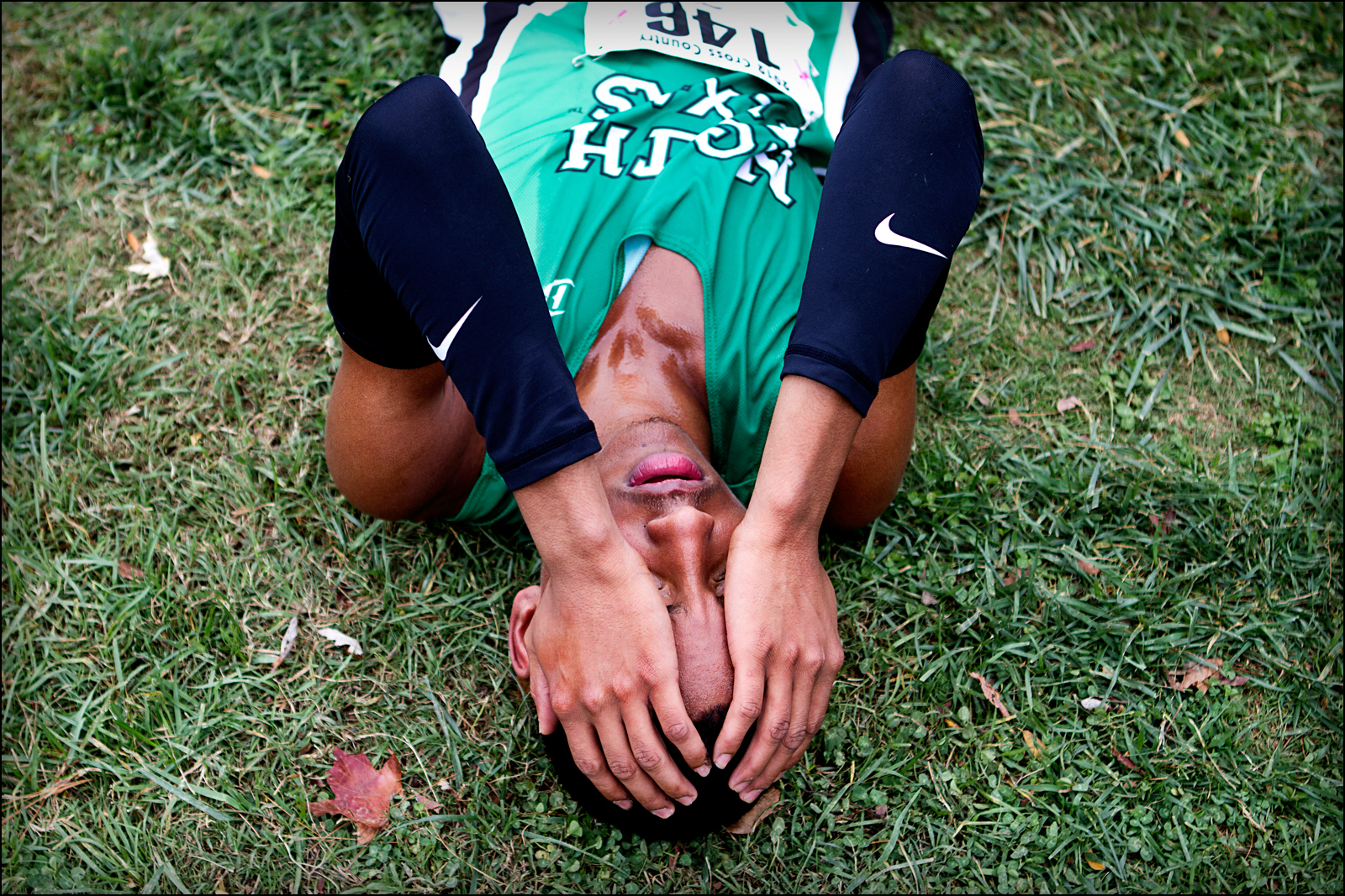 University of North Texas Silvester Harrison collapses onto the ground after finishing the mens 8K run at the Sun Belt Cross Country Championships held at Kereiakes Park in Bowling Green, KY. Harrison finished 21st to help his team finish first place in the competiton.