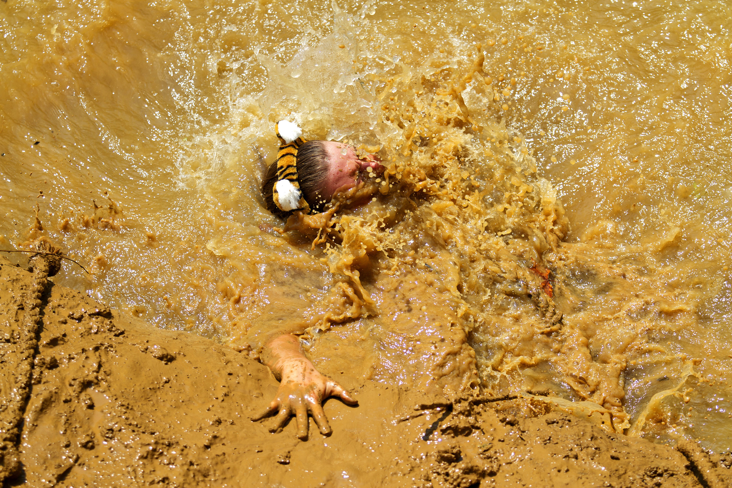 A team member from the All Cats and Dogs Team slips and falls from the top of the muddy wall and lands in the muddy water below during the Bowling Green Mud Gauntlet at Phil Moore Park. The gauntlet was presented by the Family Enrichment Center in their efforts to prevent child abuse.