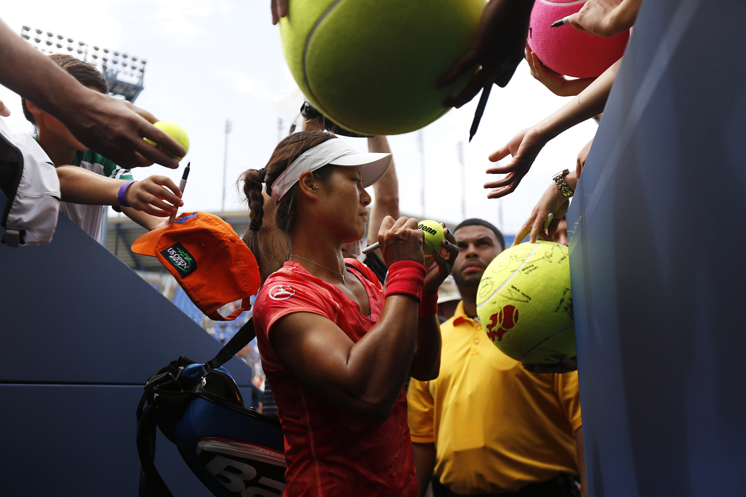 Na Li signs tennis balls after beating Olga Govortsova 6-2, 6-2. in the women singles first round at the U.S. Open tennis tournament held at Arthur Ashe Stadium in Queens, Ny.