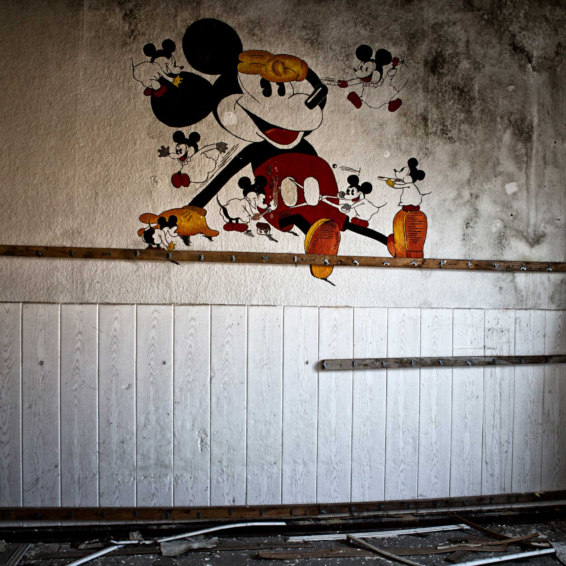 An old painting of Mickey Mouse painting on the wall of what was a child's room.When the nearby glass factory shut down the residences moved leaving the neighborhood abandoned.
