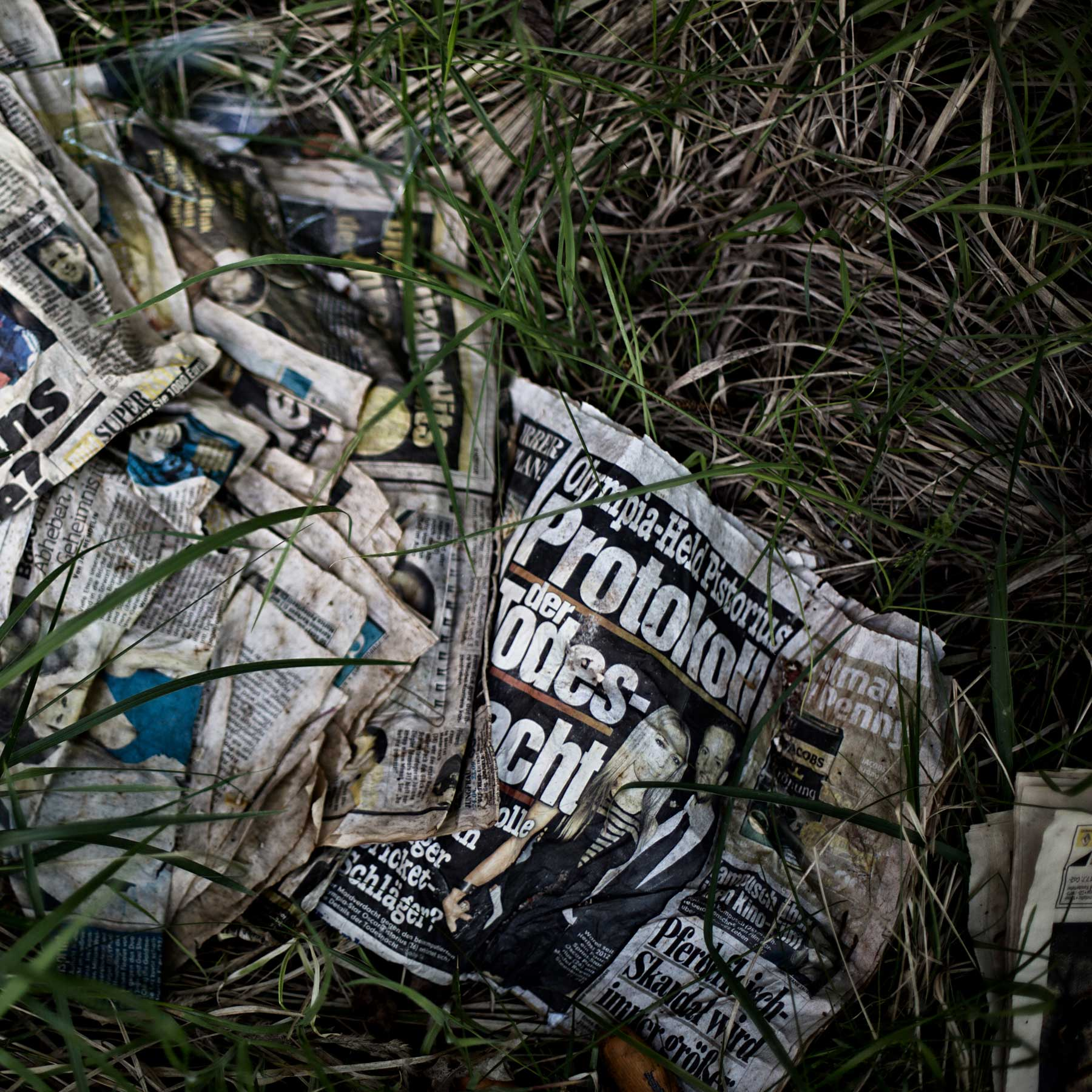 Old newspapers lay in the tall grass outside of an abandoned community.