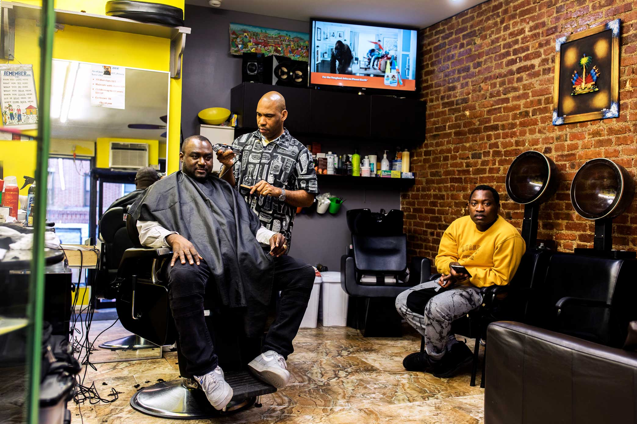 "Ben Flambert, 42, left, at a Haitian-owned barbershop in Brooklyn, supports the idea of a Little Haiti district. ""The Haitian presence out here is real strong,"" he said. ""It makes sense."""