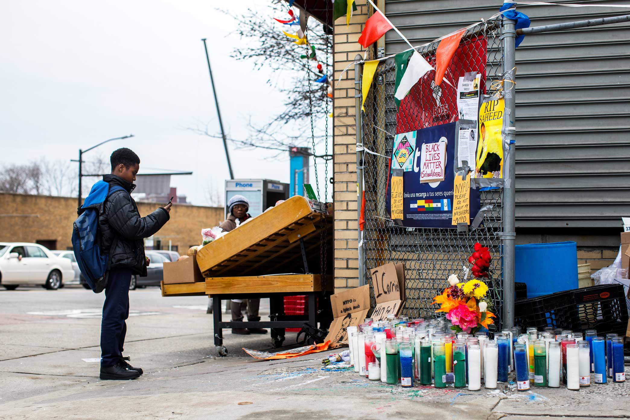 A young boy takes a photo of the memorial site for Saheed Vassell in Crown Heights, Brooklyn. Broken glass remain scattered on the ground where Saheed was shot.    The New York Times Story Link:   A Father Asks, 'Why Did They Have to Just Kill Him?'    Police Release First Details of Officers Who Shot Man in Brooklyn    Locals Knew He Was Mentally Ill. The Officers Who Shot Him Did Not.