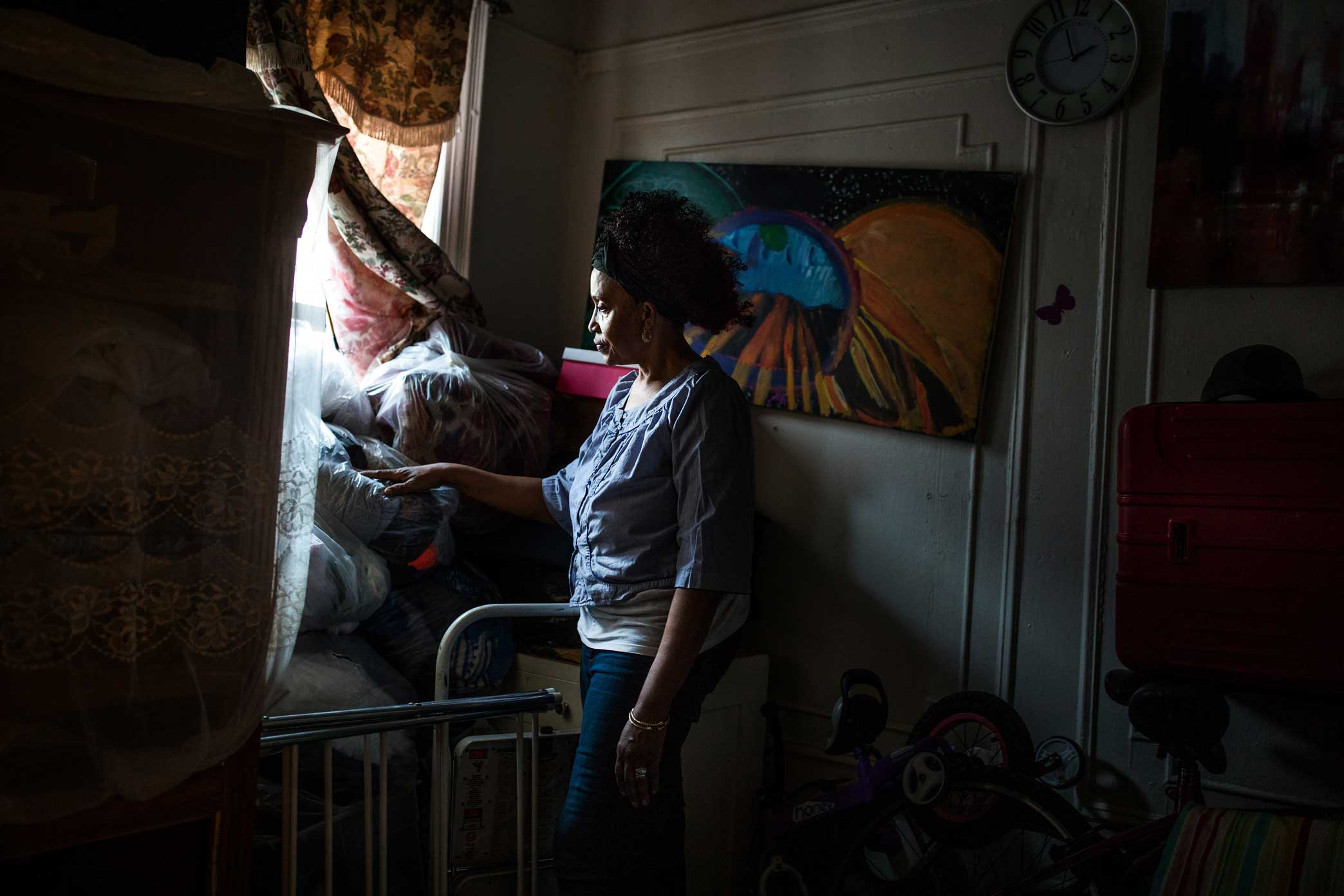Lorna Vassell goes through her son Saheed's room at the family home in Crown Heights, Brooklyn.