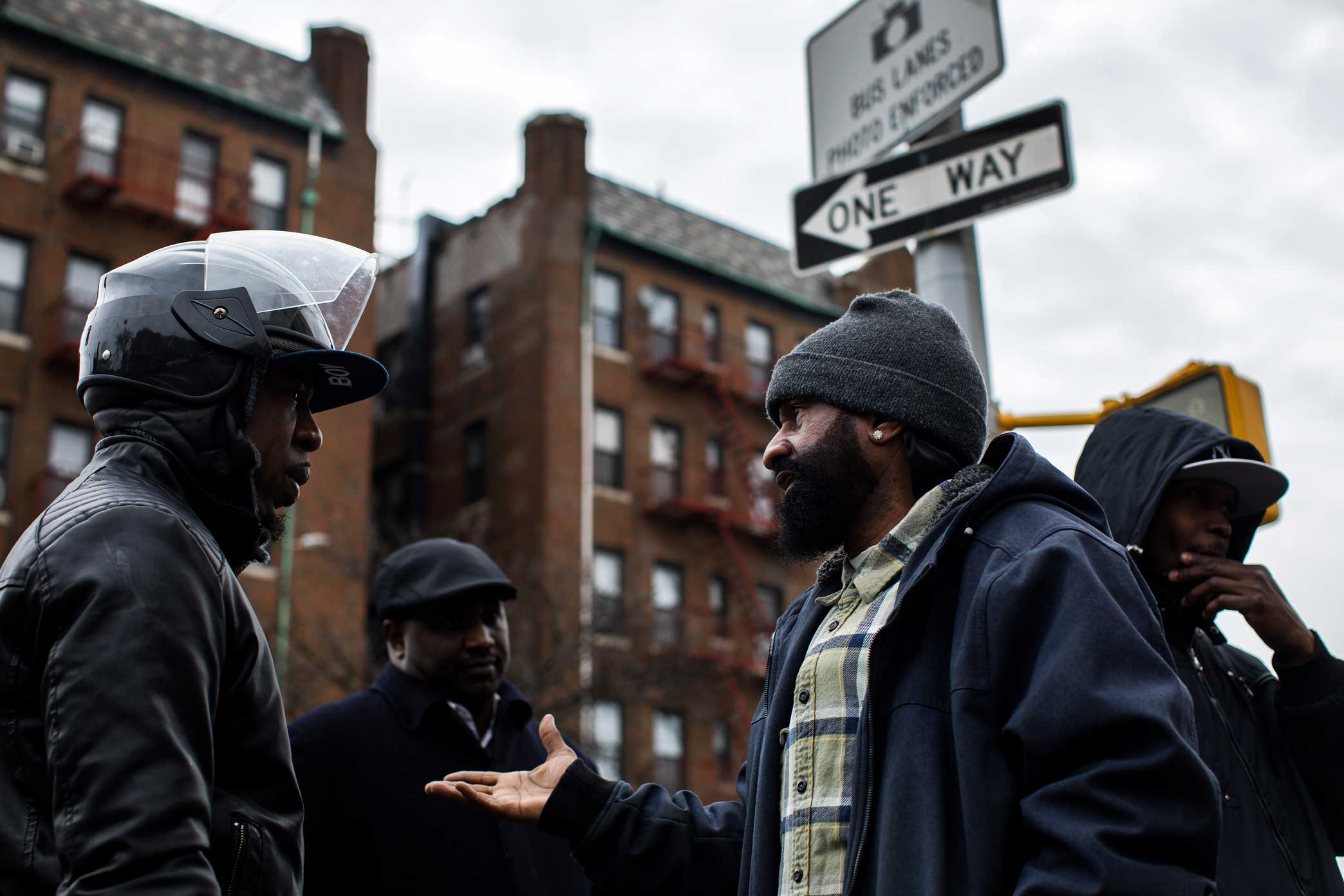 Micheal Thomas, middle, discuss with community member the problems with policing and their training at the memorial site for Saheed Vassell in Crown Heights Brooklyn.