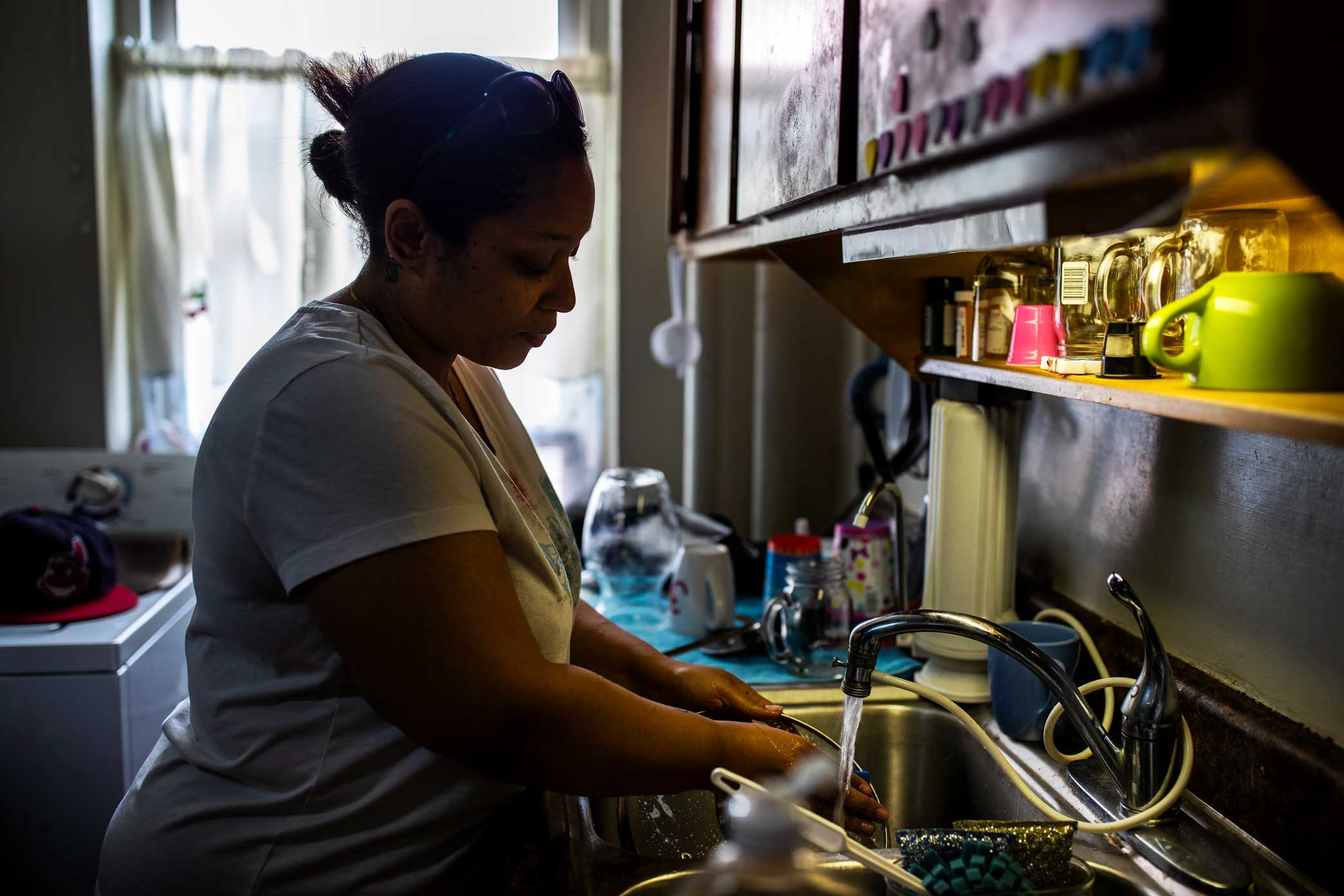 Shaly Ramirez washes dishes in her apartment.