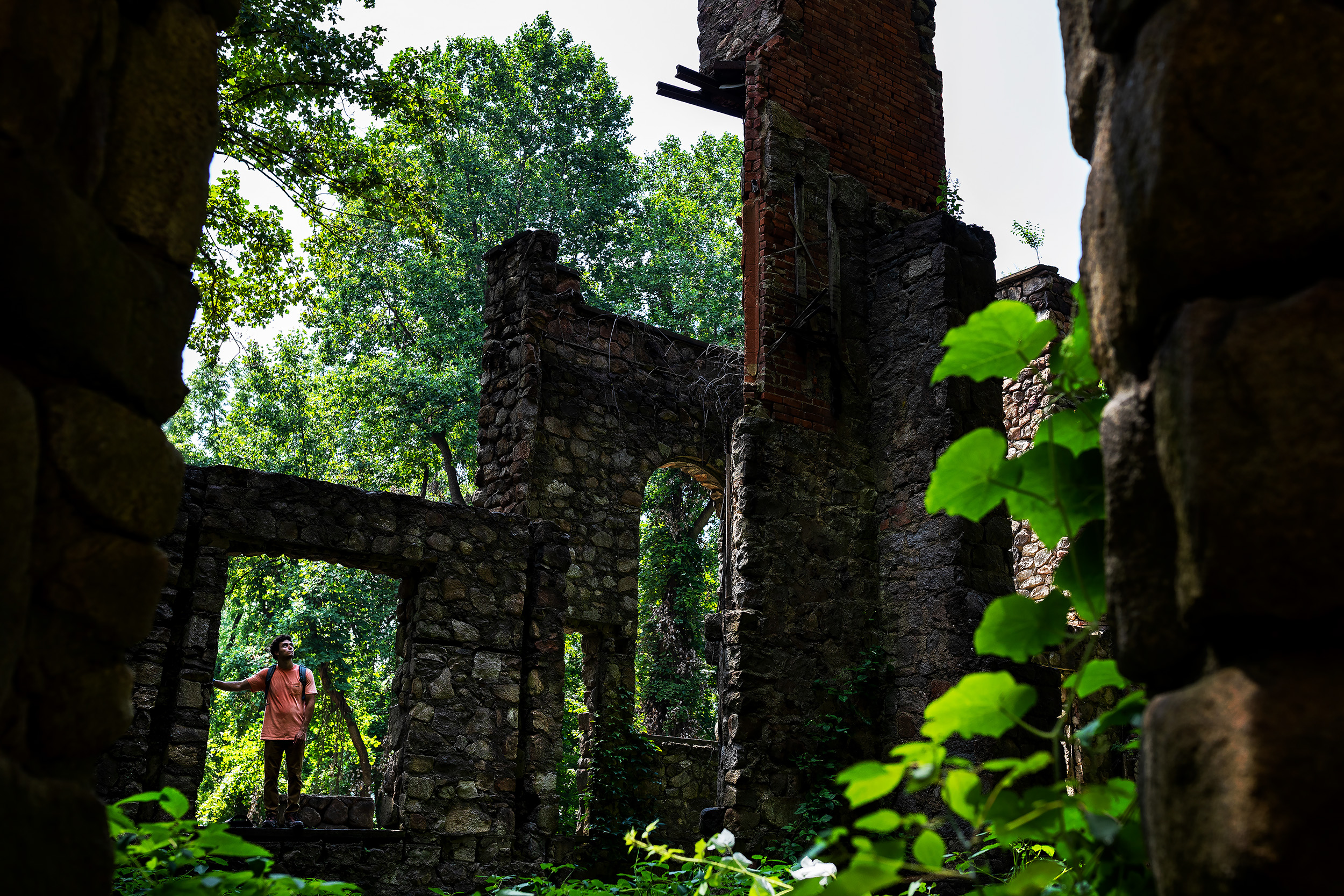 A visitor tours the old ruins of the Cornish Estate in Cold Spring, New York. In 1958, a fire destroyed most of the mansion leaving the Cornish's grand estate in ruins. Today those ruins are overgrown and gradually have been reclaimed by the forest.