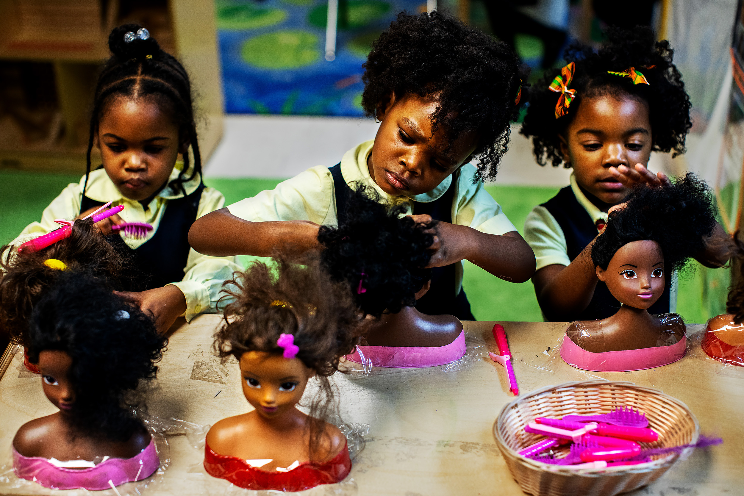 """""""Little Sun Girls""""  Students at the Little Sun People Private Preschool do the hair of dolls during play time in Brooklyn, New York.  Though New York City has tried to desegregate its schools since the 1954 Supreme Court ruling in Brown v. Board of Education, the school system is now one of the most segregated in the nation. But rather than pushing for integration, some black parents in Bedford-Stuyvesant are choosing an alternative: schools explicitly designed for black children."""
