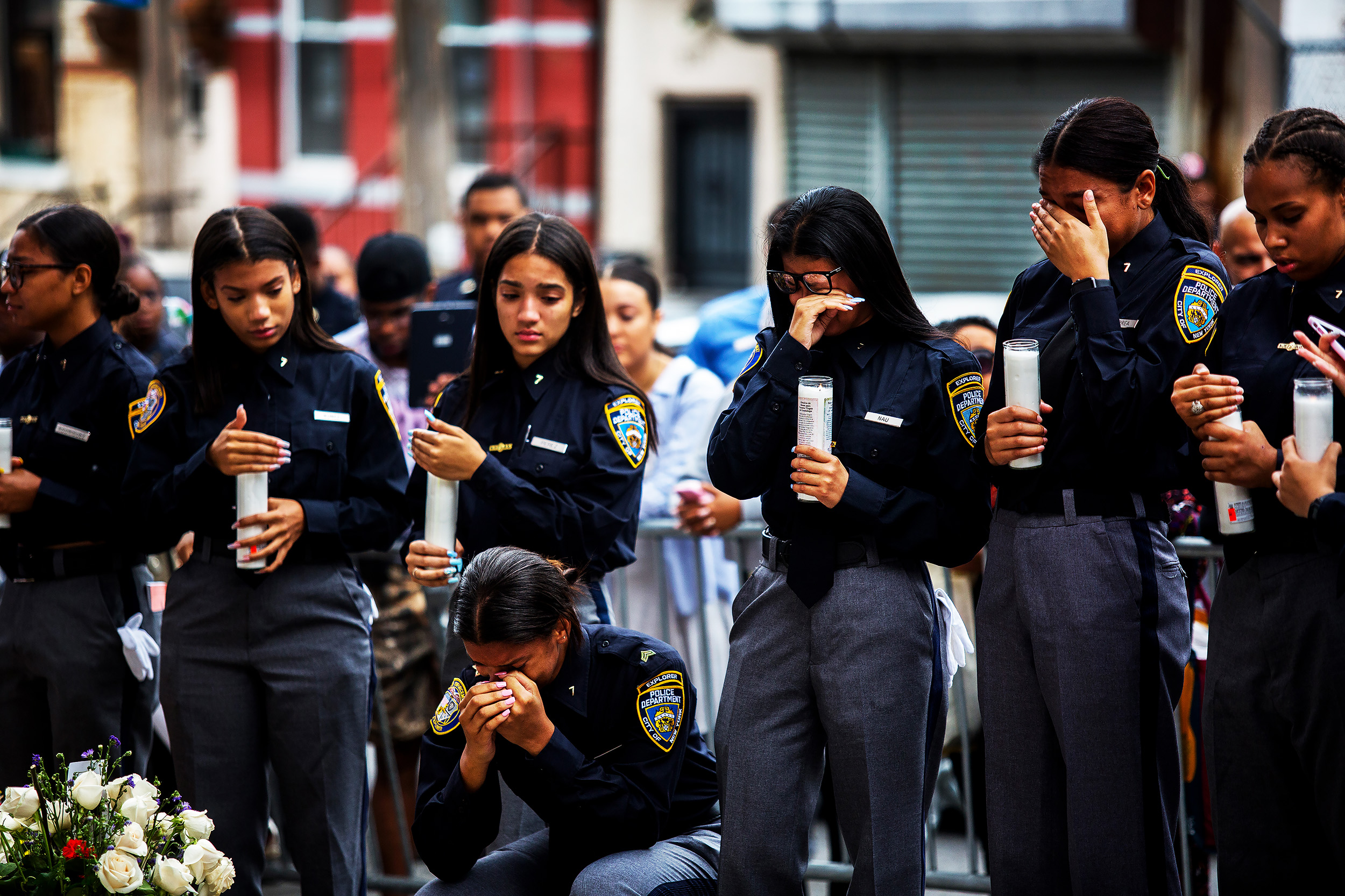 Members of the Law Enforcement Explorers program, a New York Police Department program for high school students, light candles at the makeshift memorial space for Lesandro Guzman-Feliz in the Bronx on June 27, 2018. Hundreds attended the funeral of the 15-year-old, known as Junior, whose fatal stabbing was caught on video and stunned the city.