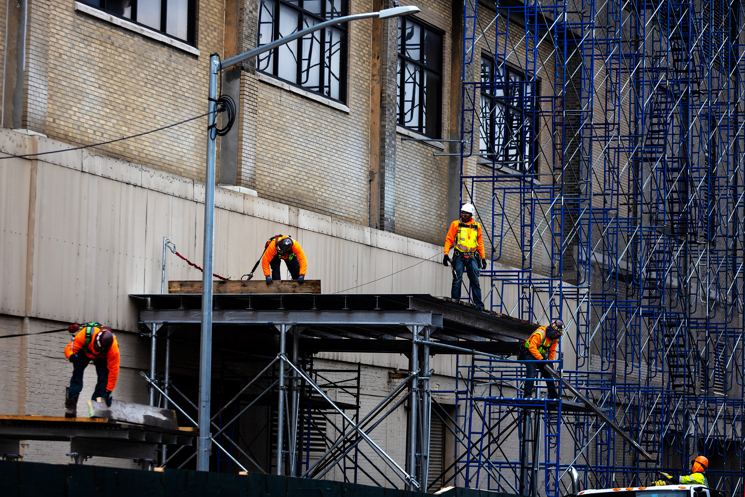 Construction workers putting up scaffold on the outside of the St. John Terminal In Manhattan, New York. Google has confirmed to expand their workforce by 7,000 workers and to add a $1 billion campus in New York City.