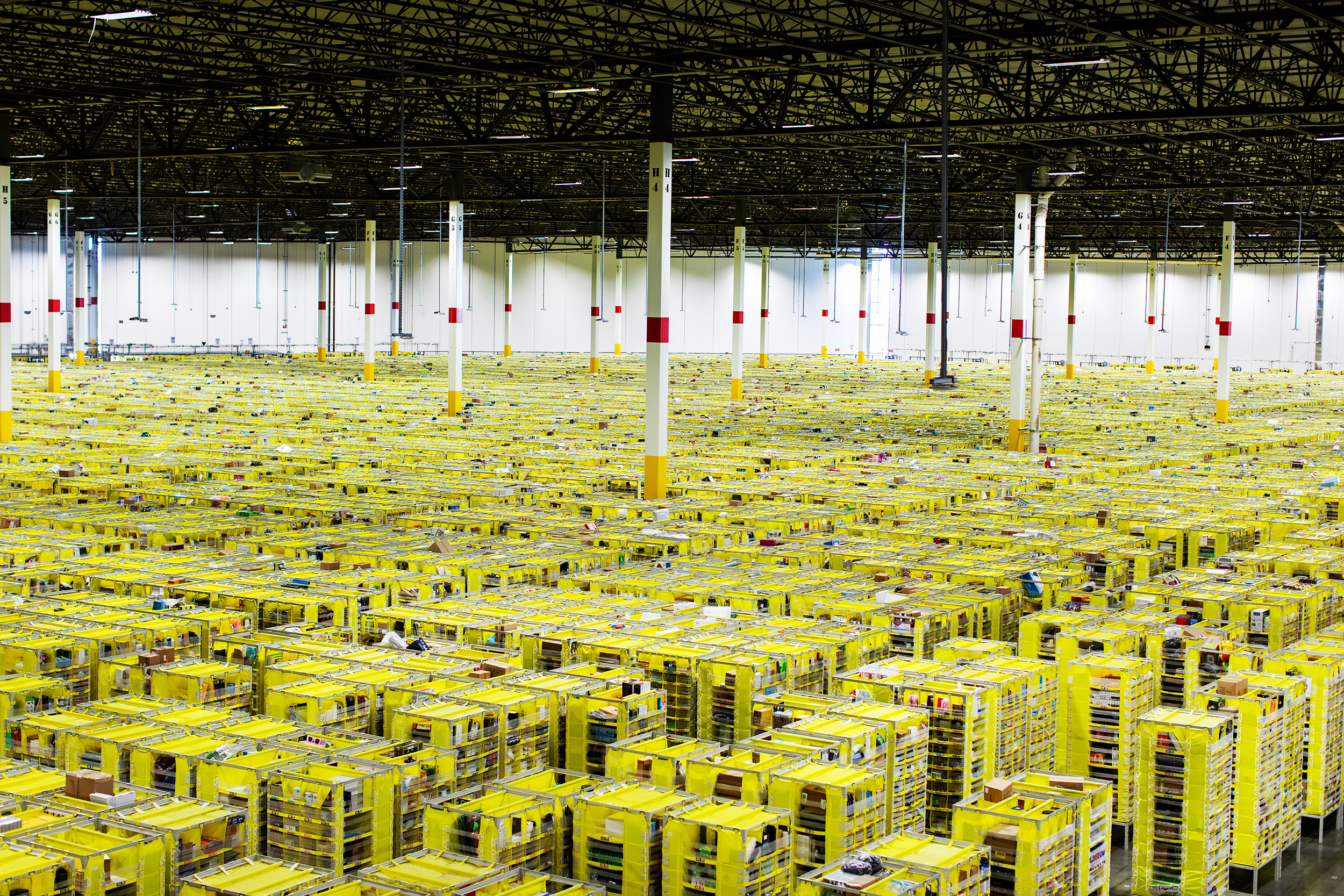 Shelves with product are organized and moved around by Amazon robots inside of the Amazon Fulfillment Center in Carteret, NJ. Workers sort products in different bins, box them and send them out for delivery.