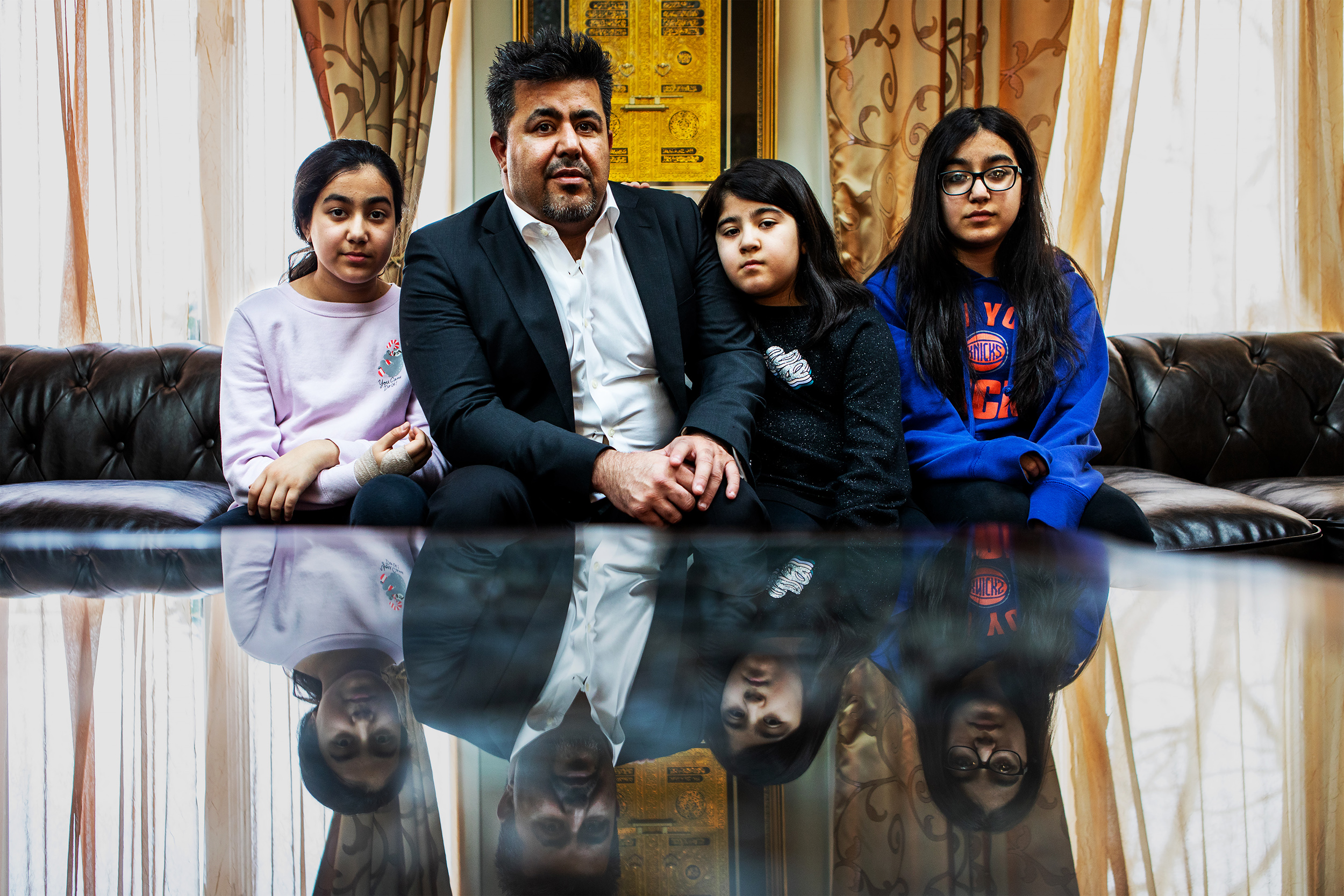 Wali Omarkheil with his children at his home in Commack, New York. Wali was discriminated against because of his religion and was eventually fired. He is now suing the corporation that fired him.