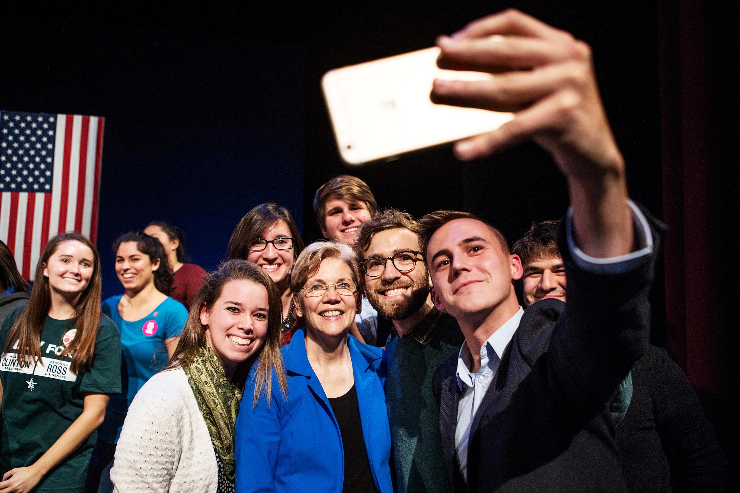 Elizabeth Warren takes a selfie after a campaign speech.